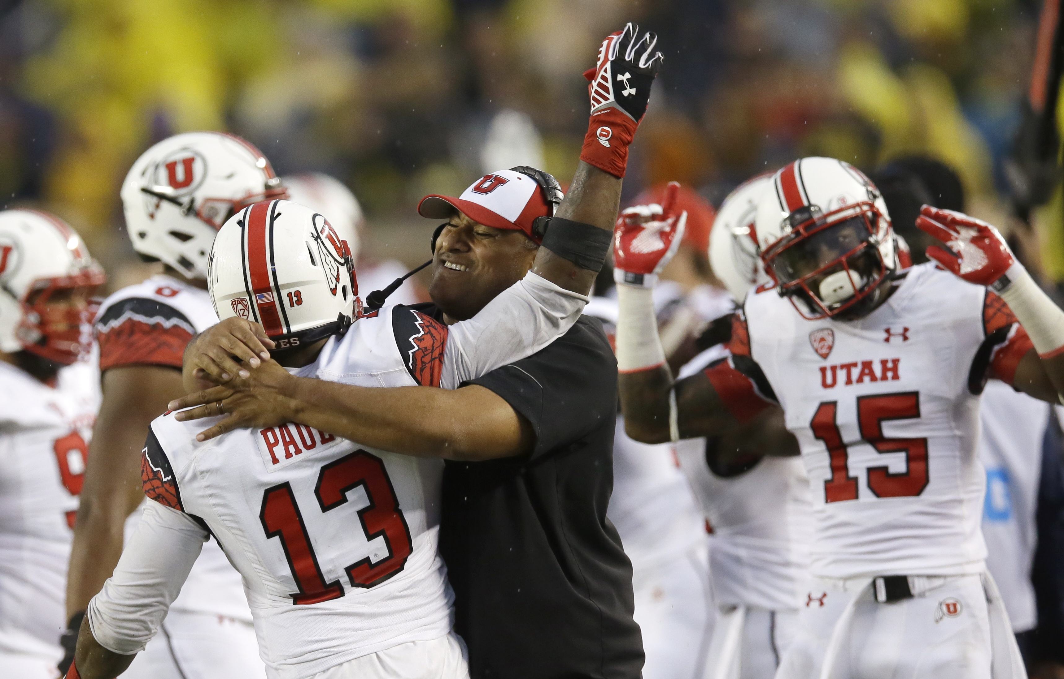 Utah linebacker Gionni Paul (13) is hugged by Assistant Head Coach Kalani Fifita Sitake on the sidelines after he intercepted a pass from Michigan quarterback Devin Gardner during the second half of an NCAA college football game in Ann Arbor, Mich., Satur