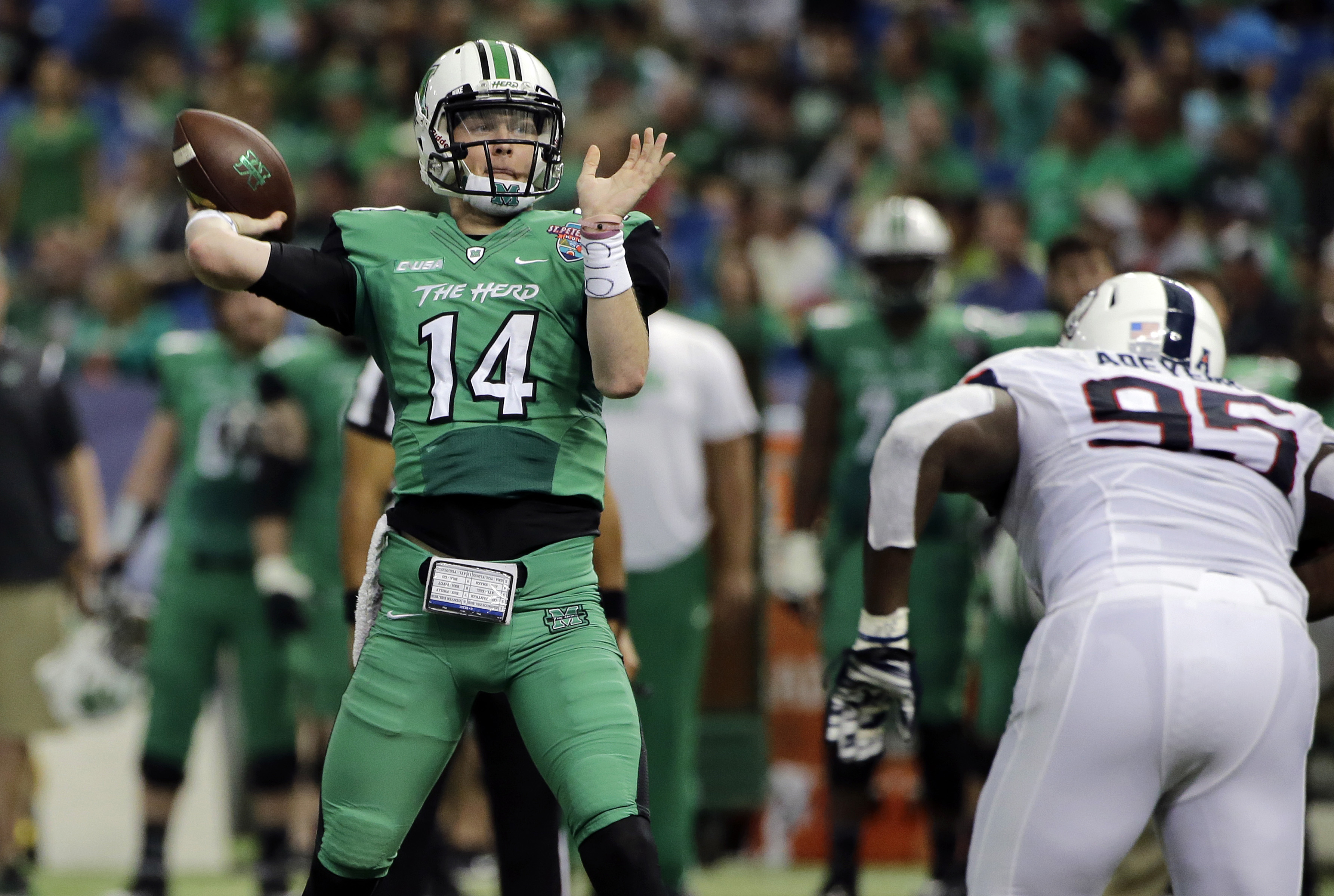 Marshall quarterback Chase Litton (14) is pressured by Connecticut defensive lineman Kenton Adeyemi (95) as he throws a touchdown pass to tight end Ryan Yurachek during the first quarter of the St. Petersburg Bowl NCAA college football game, Saturday, Dec
