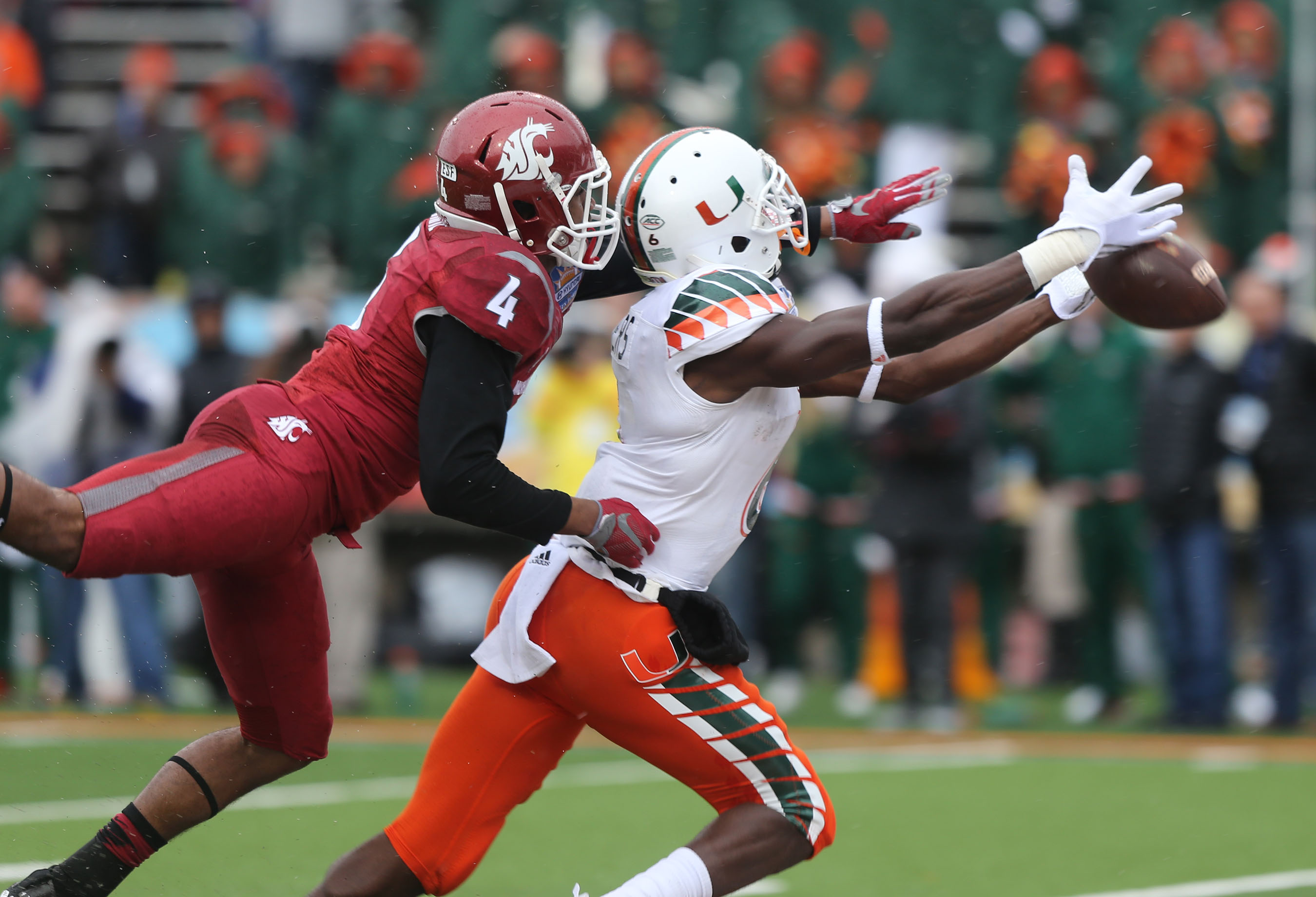 Miami receiver Herb Waters stretches to reach a long pass in front of Washington State defender Charleston White during the first half of the Sun Bowl NCAA college football game Saturday Dec. 26, 2015 in El Paso, Texas. (AP Photo/Victor Calzada)