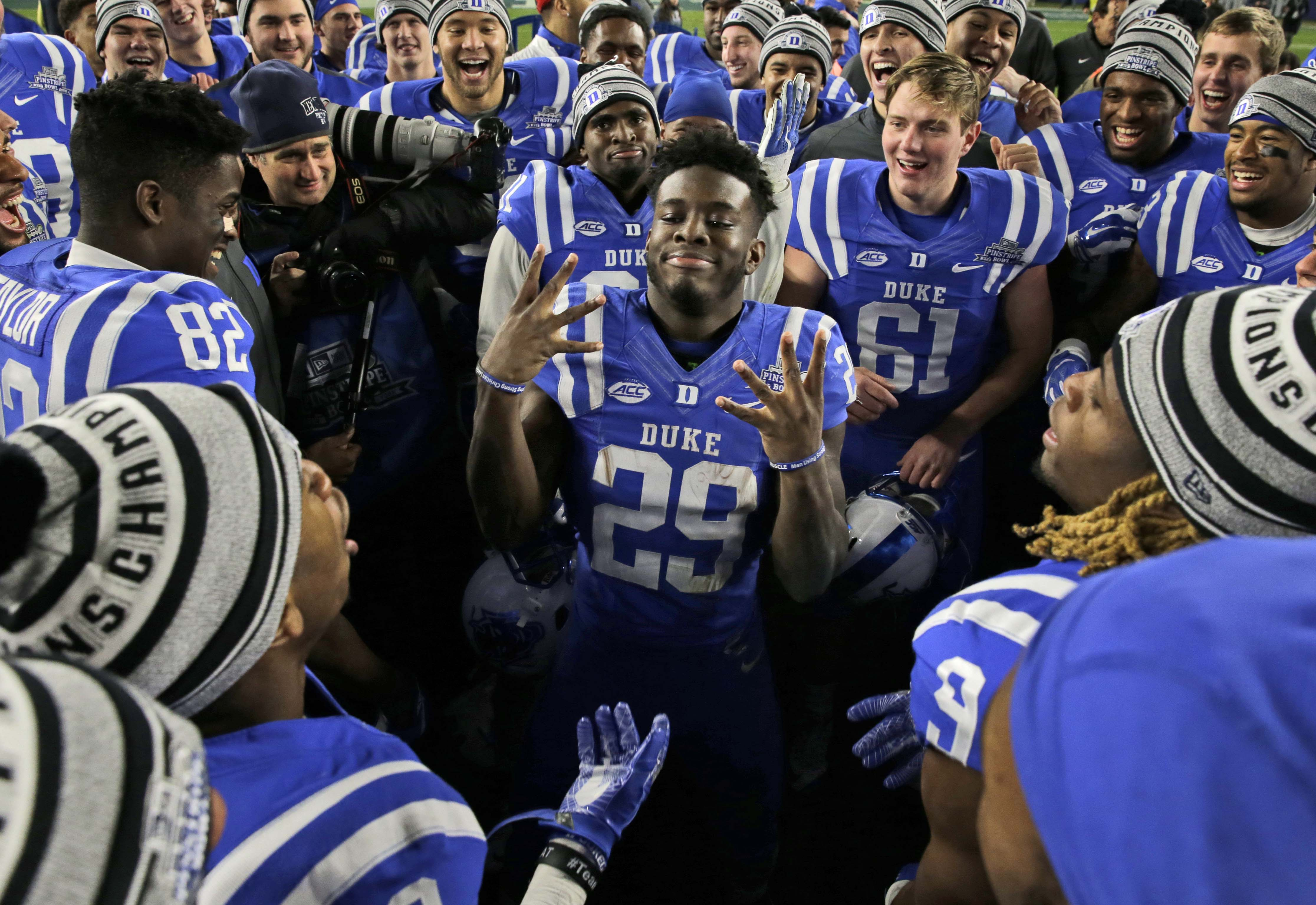 Duke's Shaun Wilson, center, celebrates with teammates after the Pinstripe Bowl NCAA college football game against Indiana at Yankee Stadium in New York, Saturday, Dec. 26, 2015. Duke defeated Indiana 44-41. (AP Photo/Seth Wenig)