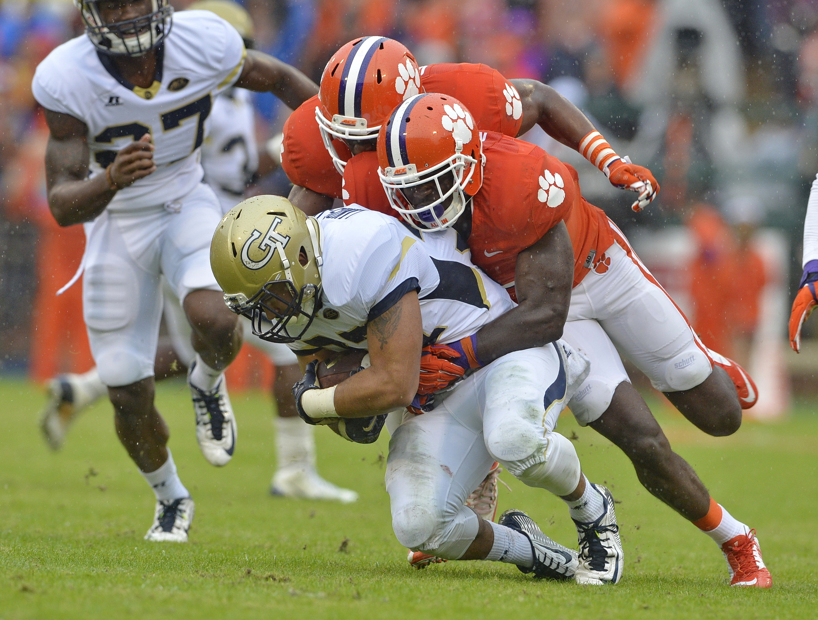 FILE - In this Oct. 10, 2015, file photo, Clemson's Jayron Kearse, center, and Richard Yeargin tackle Georgia Tech's Mikell Lands-Davis during the first half of an NCAA college football game in Clemson, S.C. No one pushes No. 1 Clemson's defense harder th