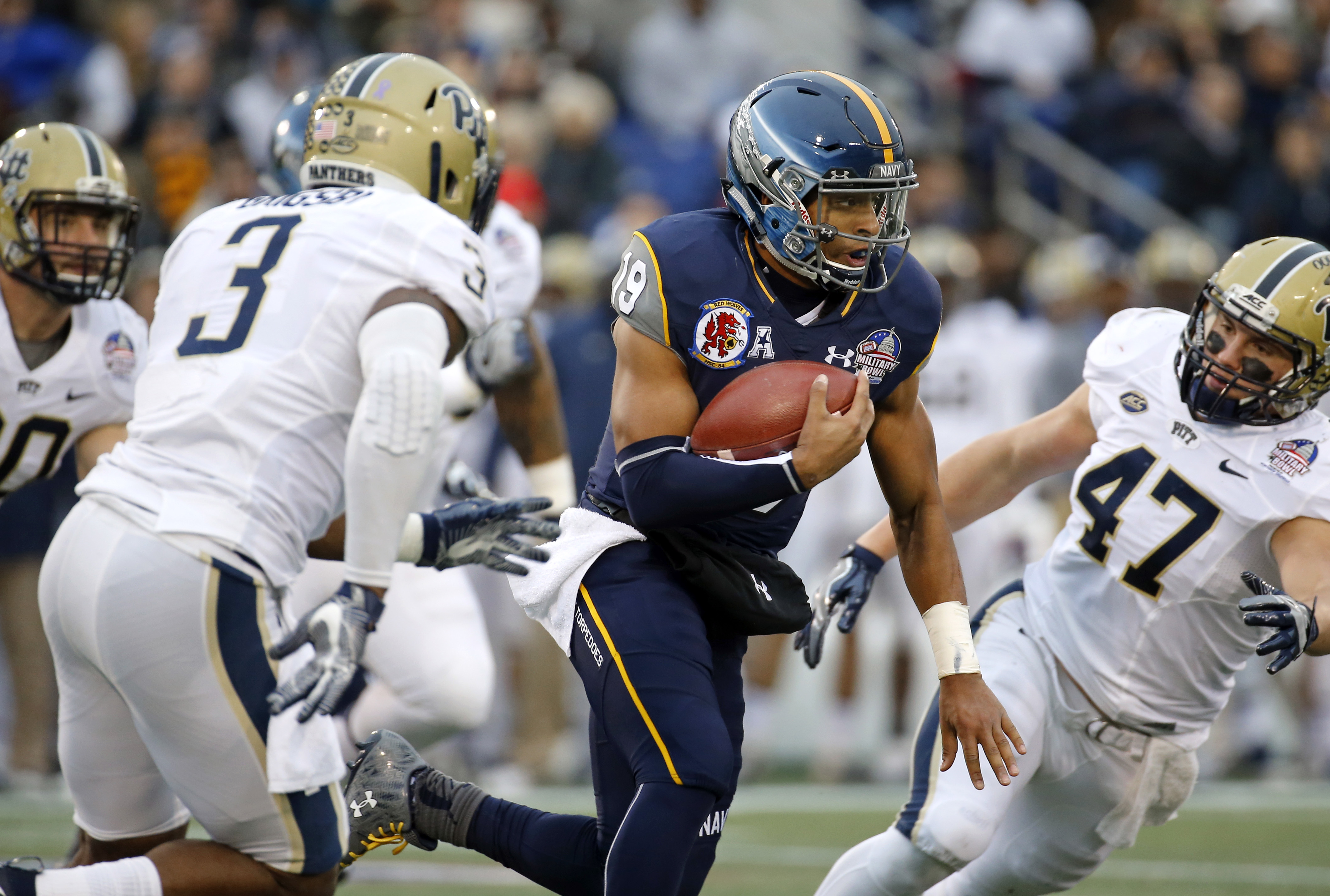 Navy quarterback Keenan Reynolds, center, rushes between Pittsburgh linebackers Nicholas Grigsby (3) and Matt Galambos (47) in the first half of the Military Bowl NCAA college football game, Monday, Dec. 28, 2015, in College Park, Md. (AP Photo/Patrick Se