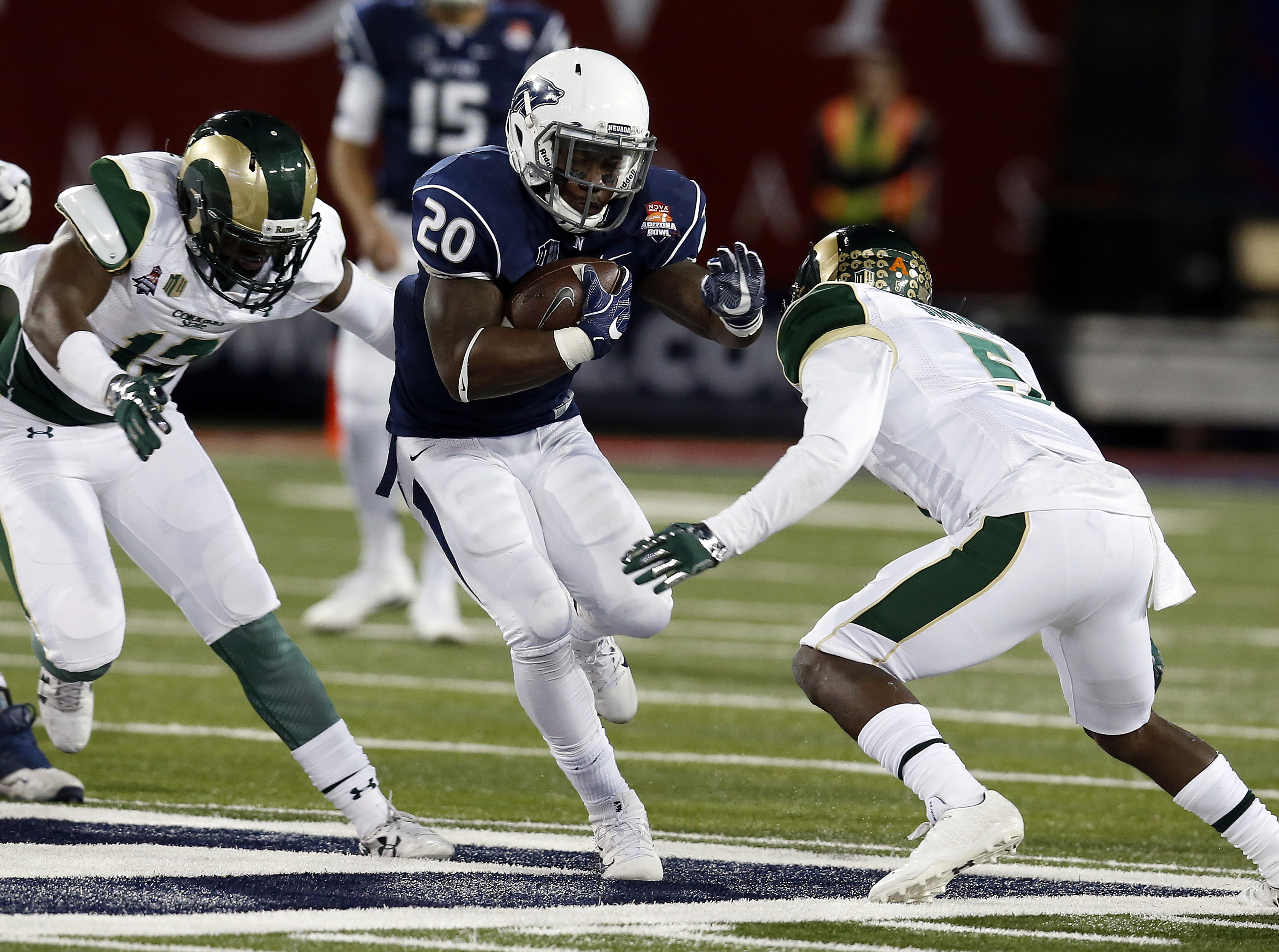 Nevada running back James Butler (20) carries the ball during the first half of the Arizona Bowl NCAA college football game against Colorado State, Tuesday, Dec. 29, 2015, in Tucson, Ariz. (AP Photo/Rick Scuteri)