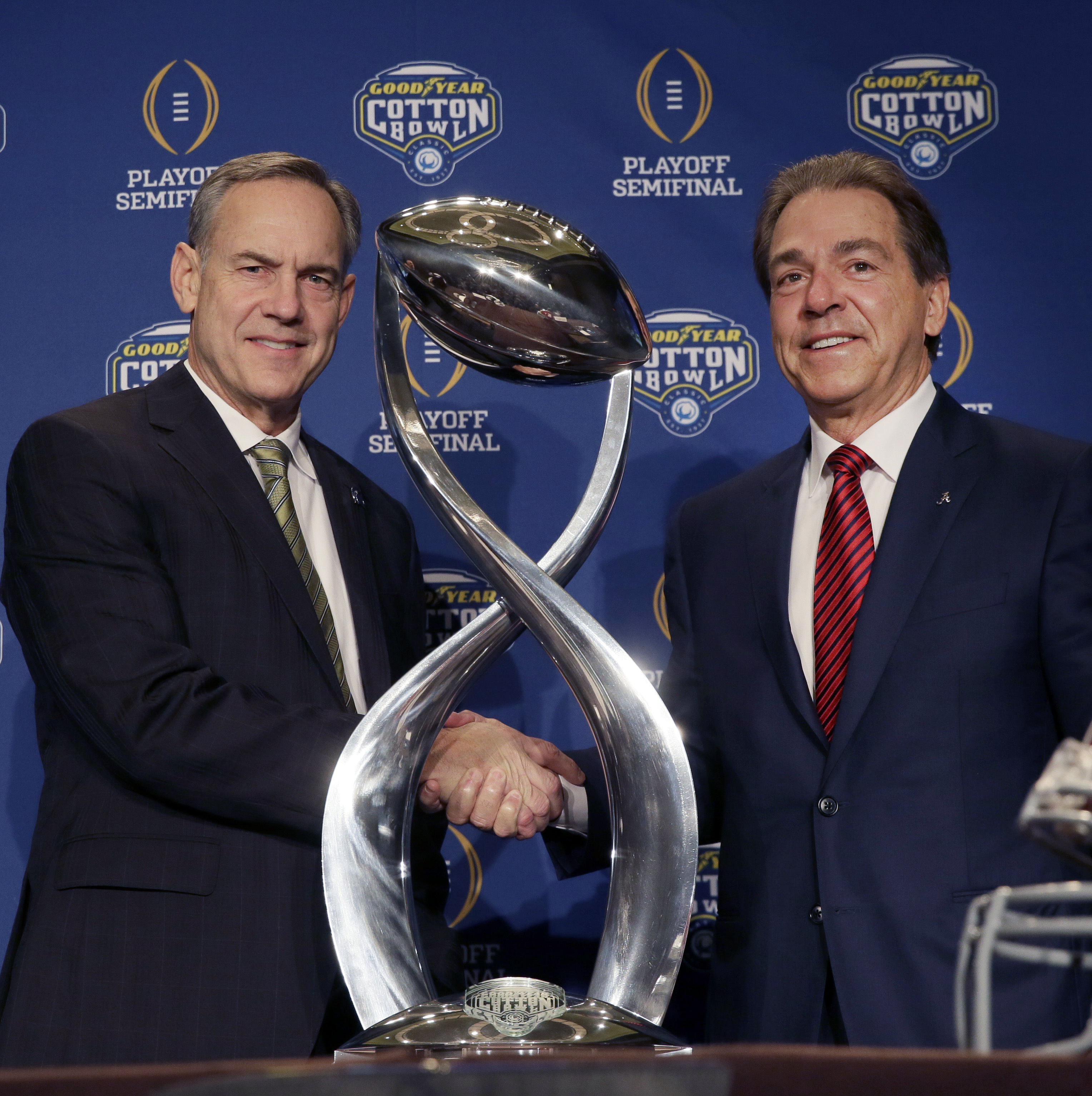 Michigan State head coach Mark Dantonio, left, and Alabama head coach Nick Saban  shake hands and pose for after a news conference for the Cotton Bowl NCAA college football game Wednesday, Dec. 30, 2015, in Arlington, Texas. Alabama and Michigan State fac
