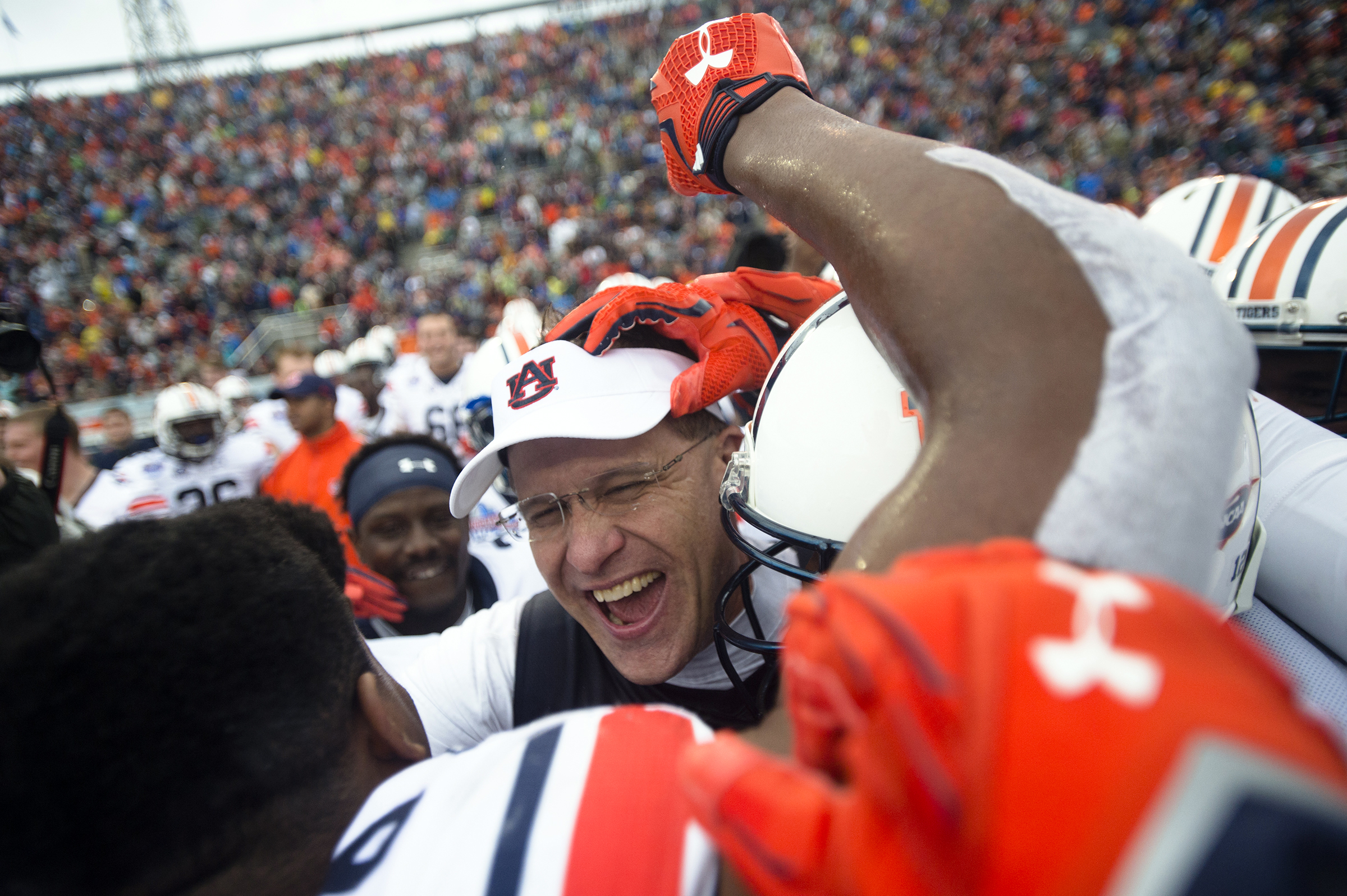 Auburn coach Gus Malzahn, center, celebrates with his players after they defeated Memphis 31-10 in the Birmingham Bowl NCAA college football game, Wednesday, Dec. 30, 2015, in Birmingham, Ala. (Albert Cesare/The Montgomery Advertiser via AP)  NO SALES; MA