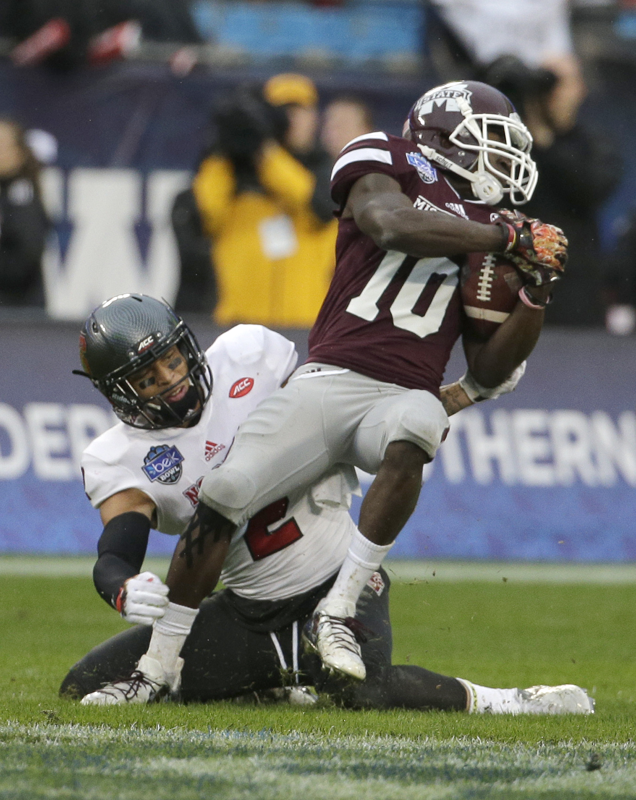 Mississippi State running back Brandon Holloway (10) catches a pass as North Carolina State safety Josh Jones (2) defends in the first half of the Belk Bowl NCAA college football game in Charlotte, N.C., Wednesday, Dec. 30, 2015. (AP Photo/Chuck Burton)