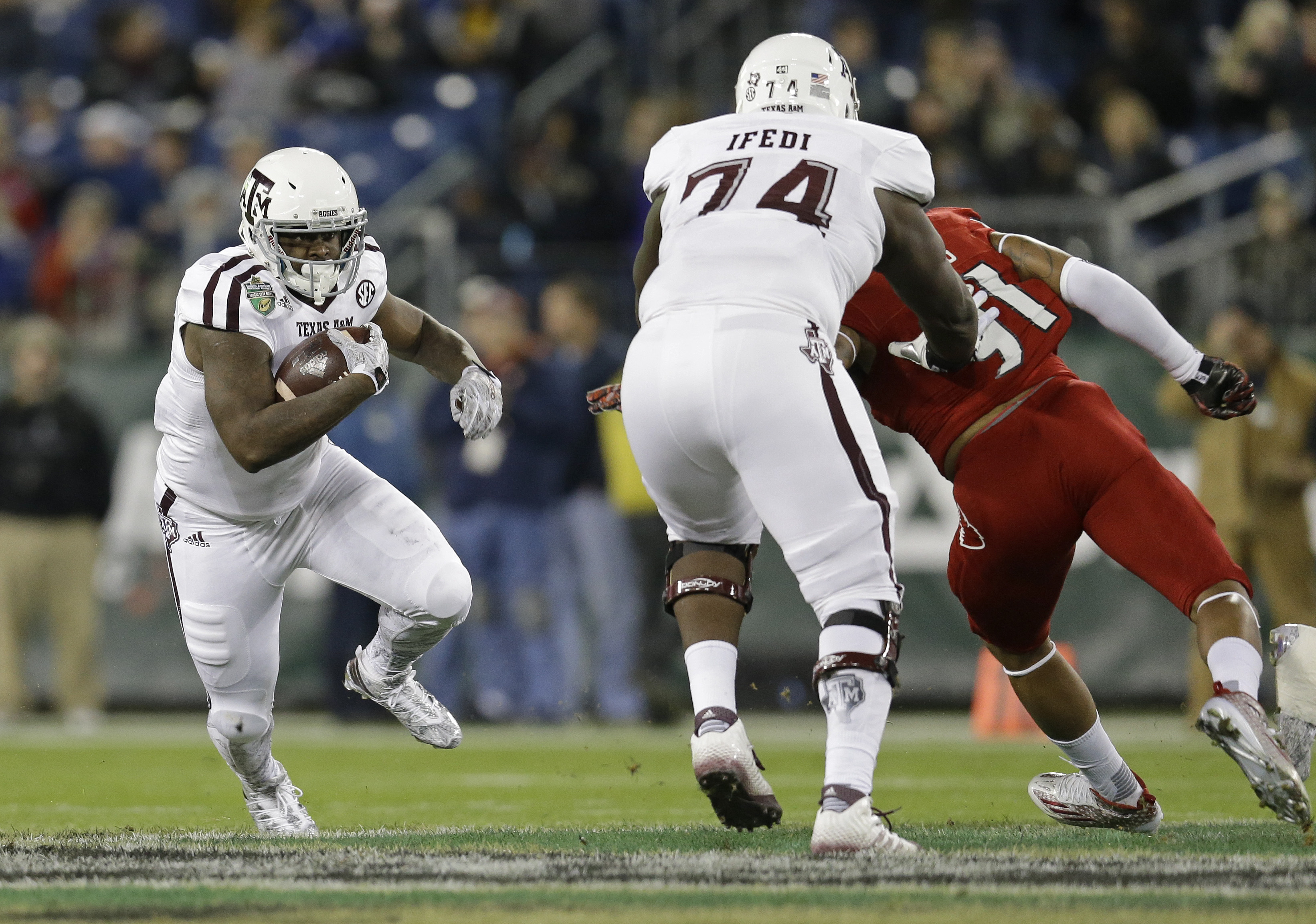 Texas A&M running back Tra Carson, left, follows a block by offensive lineman Germain Ifedi (74) on Louisville linebacker Trevon Young (91) in the first half of the Music City Bowl NCAA college football game Wednesday, Dec. 30, 2015, in Nashville, Tenn. (