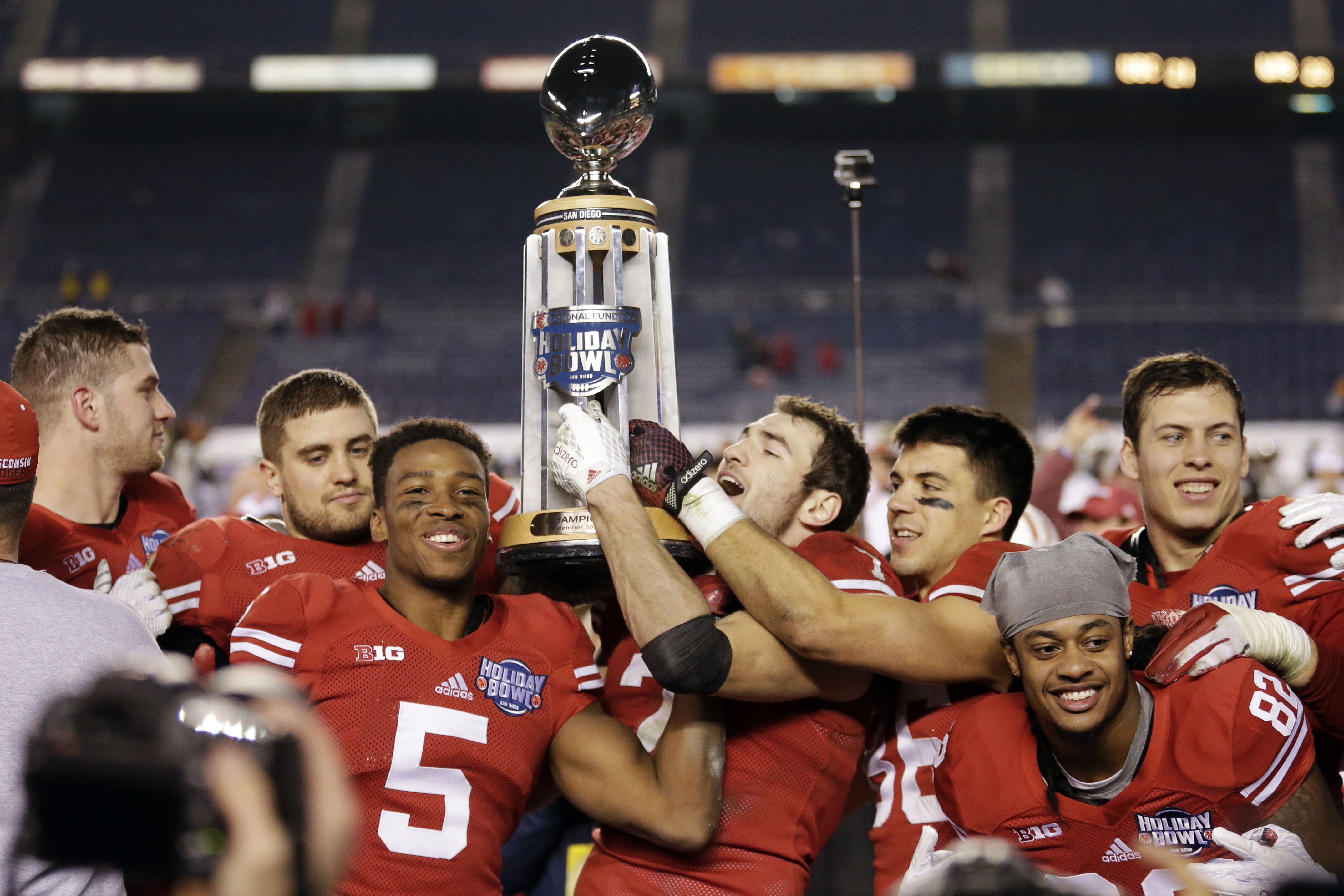 Wisconsin players hold the Holiday Bowl trophy after defeating Southern California in the Holiday Bowl NCAA college football game Wednesday, Dec. 30, 2015, in San Diego. Wisconsin won 23-21. (AP Photo/Gregory Bull)