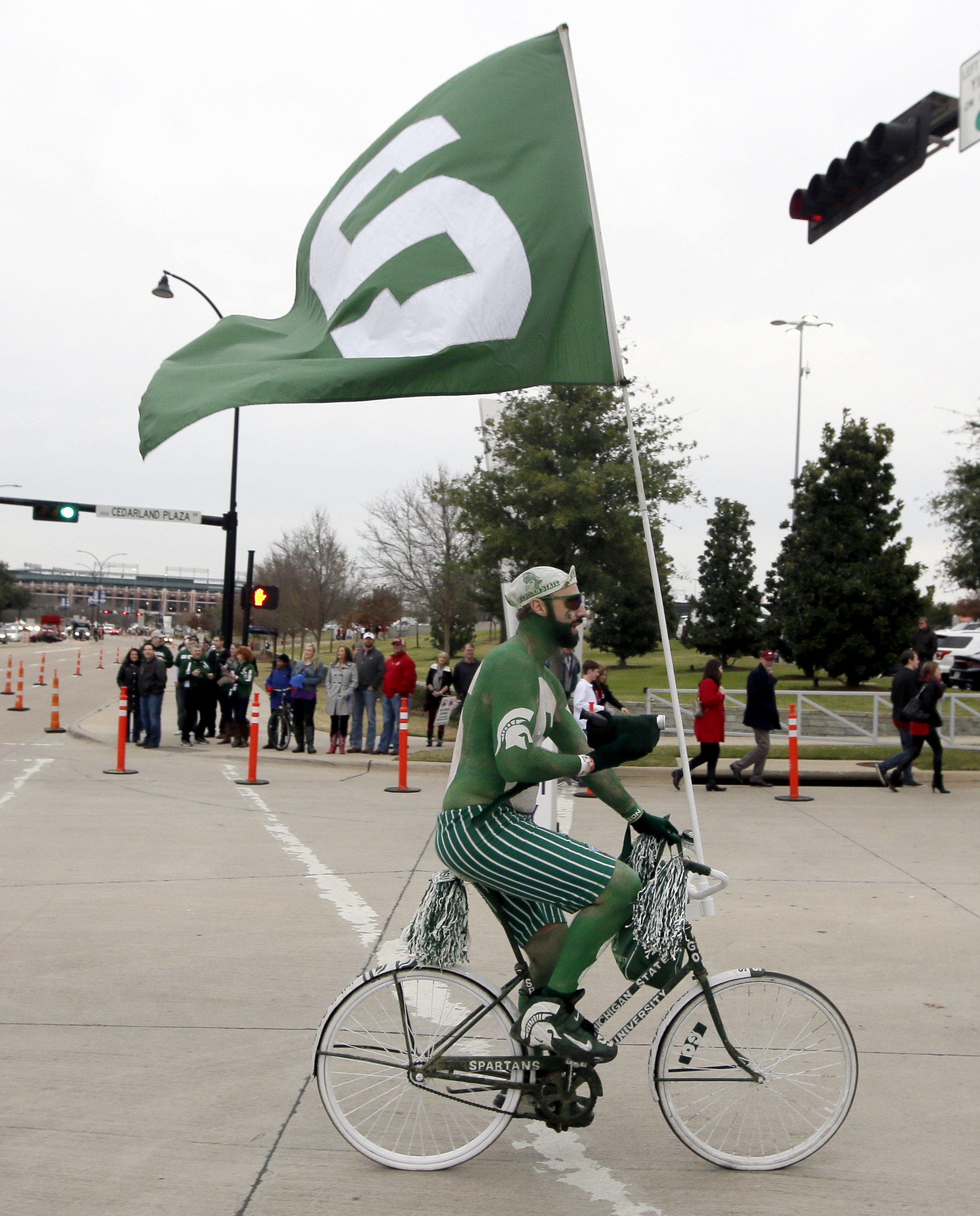 A Michigan State fan rides around AT&T Stadium before the Cotton Bowl NCAA college football semifinal playoff game against Alabama, Thursday, Dec. 31, 2015, in Arlington, Texas. (AP Photo/LM Otero)