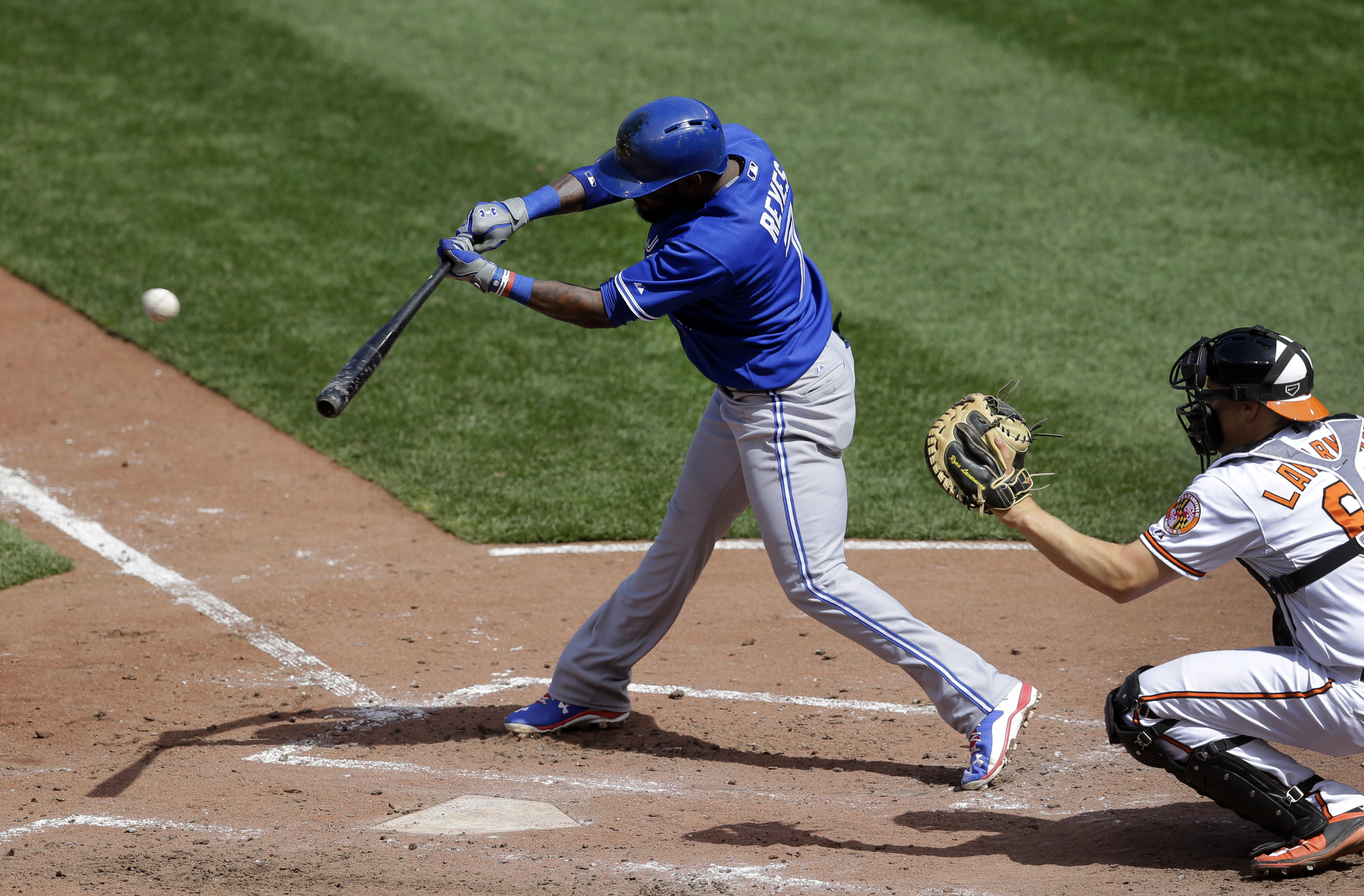 Toronto Blue Jays' Jose Reyes, left, singles in the third inning of a baseball game against the Baltimore Orioles, Sunday, April 12, 2015, in Baltimore. Blue Jays' Devon Travis scored on the play. Toronto won 10-7. (AP Photo/Patrick Semansky)