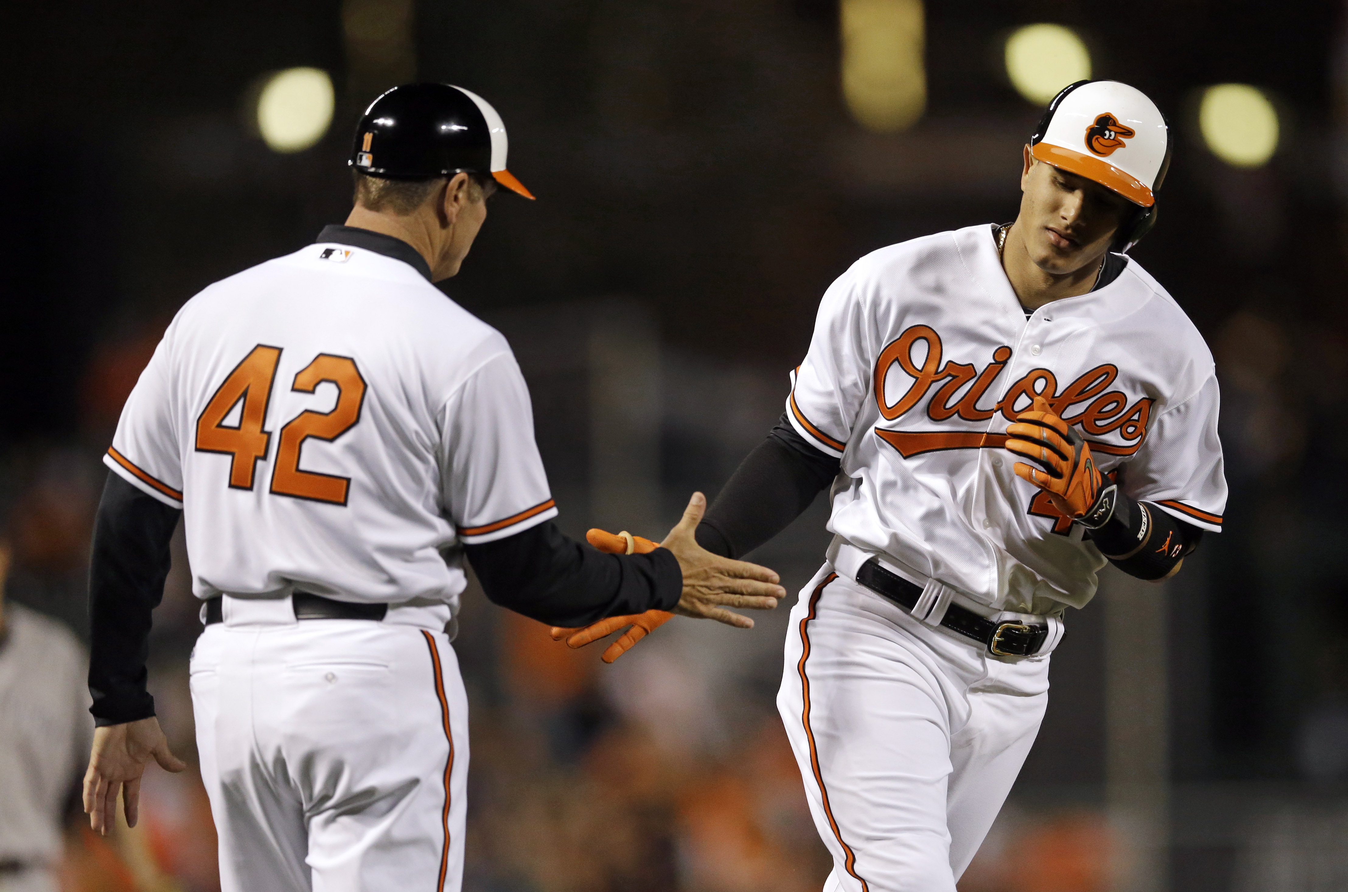 Baltimore Orioles' Manny Machado, right, greets third base coach Bobby Dickerson as he rounds the bases on a solo home run in the fourth inning of a baseball game against the New York Yankees, Wednesday, April 15, 2015, in Baltimore. (AP Photo/Patrick Sem
