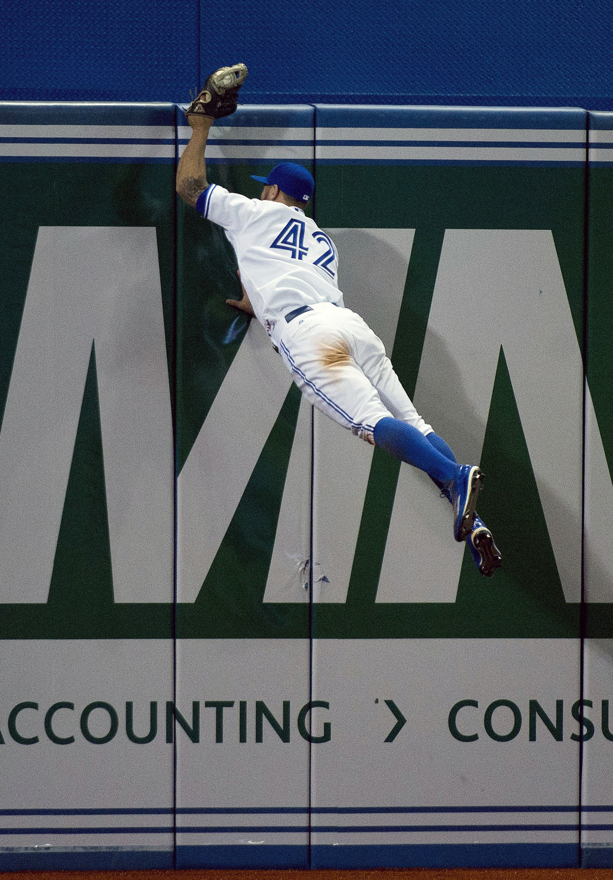 Toronto Blue Jays left fielder Kevin Pillar makes a catch on the other side of the wall hit by Tampa Bay Rays Tim Beckham during the seventh inning of a baseball game, Wednesday, April 15, 2015 in Toronto. (Nathan Denette/The Canadian Press via AP)  MANDA