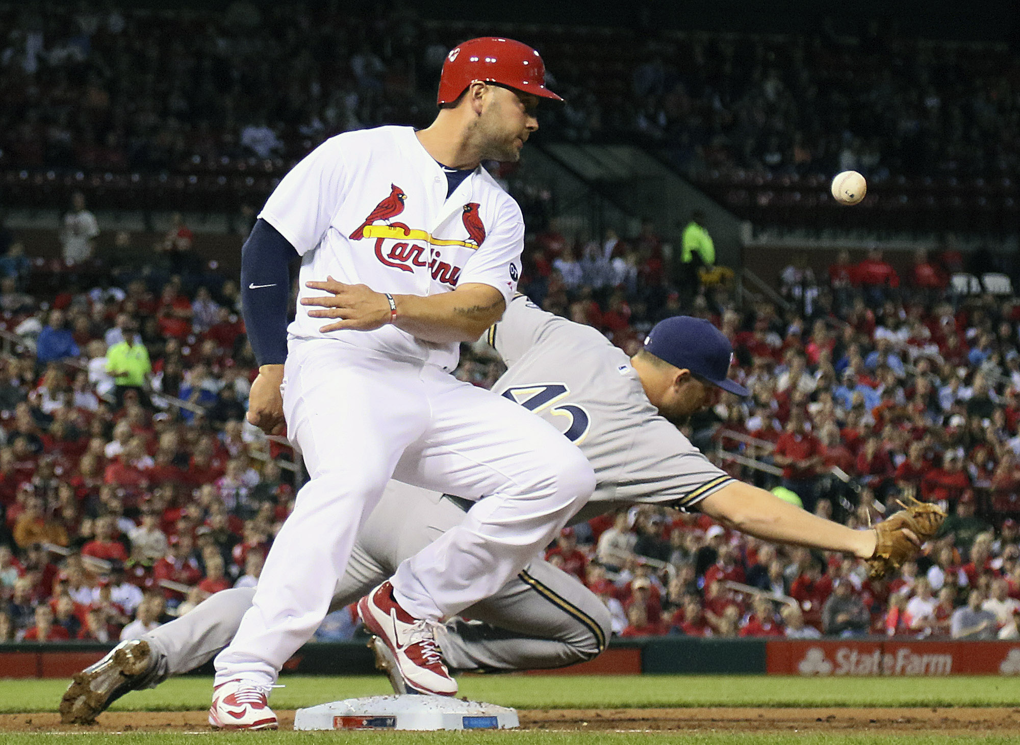 Milwaukee Brewers first baseman Adam Lind, right,  is unable to catch an errant throw from shortstop Jean Segura as St. Louis Cardinals' Matt Holliday, left, advances to second on the error in the first of a baseball game, Wednesday, April 15, 2015, in St