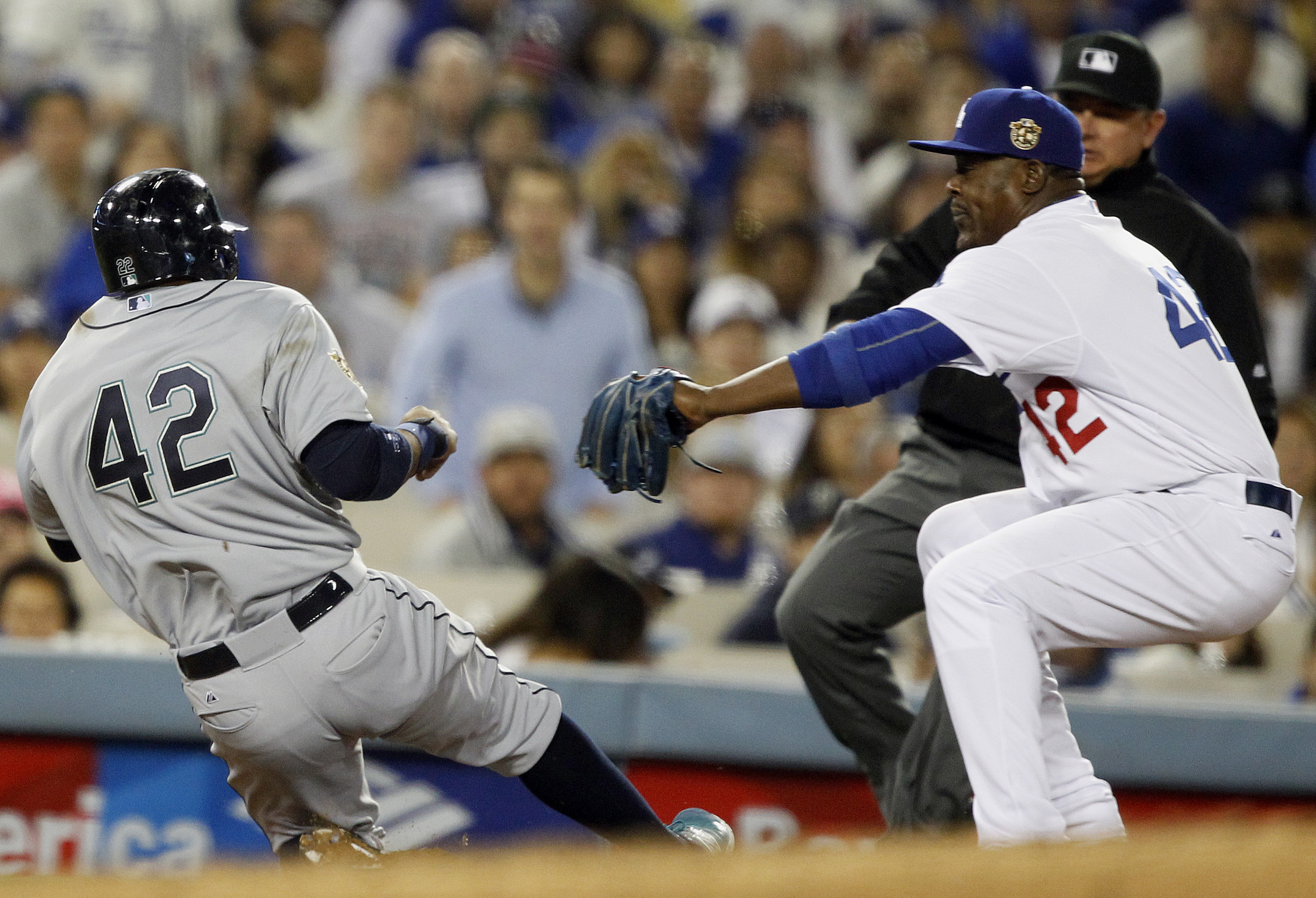 Los Angeles Dodgers third baseman Juan Uribe, right, tags out Seattle Mariners' Robinson Cano at third base in a rundown, during the sixth inning of a baseball game in Los Angeles, Wednesday, April 15, 2015. (AP Photo/Alex Gallardo)