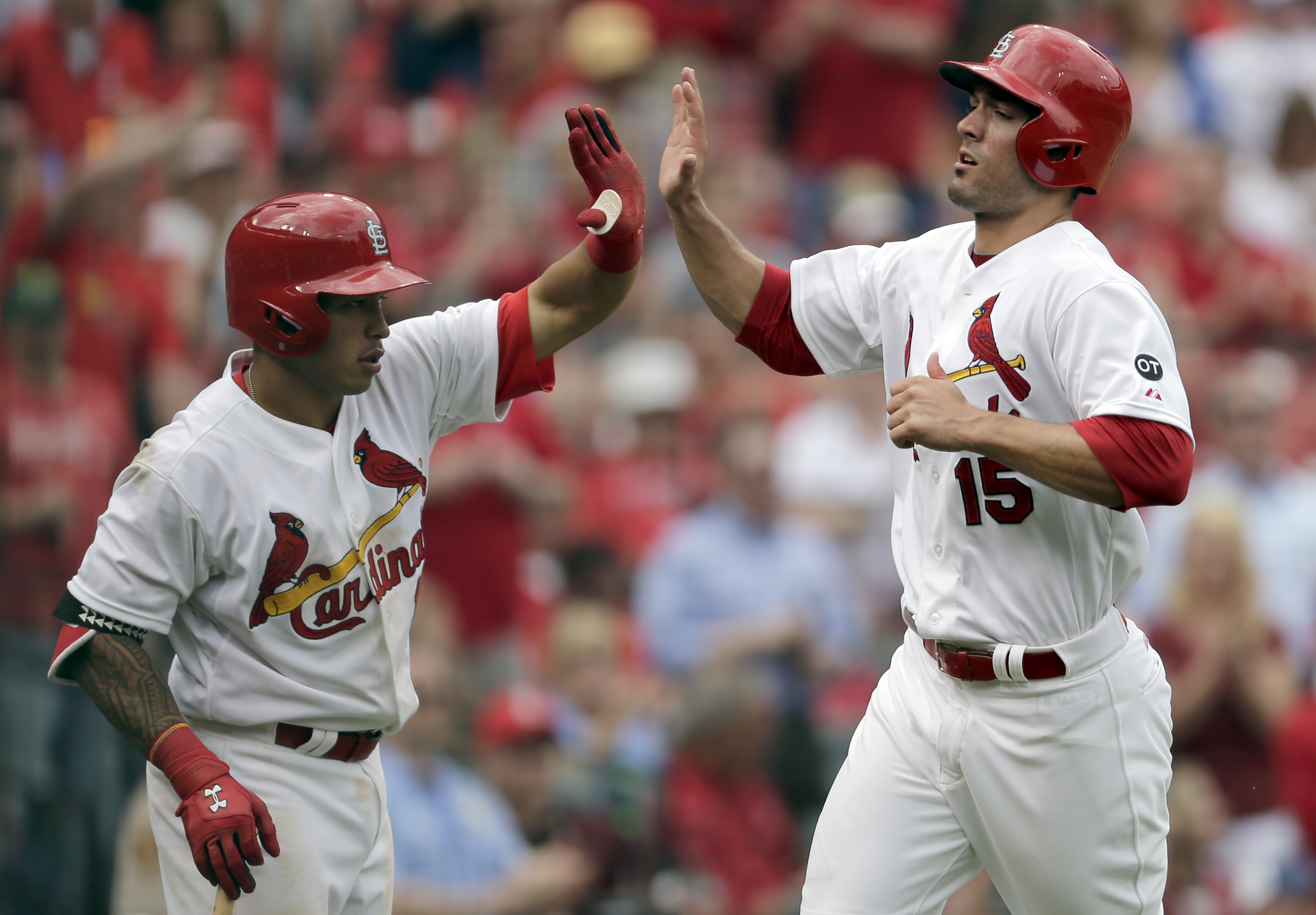 St. Louis Cardinals' Randal Grichuk, right, is congratulated by teammate Kolten Wong after scoring on a single by Yadier Molina during the eighth inning of a baseball game against the Milwaukee Brewers Thursday, April 16, 2015, in St. Louis. (AP Photo/Jef
