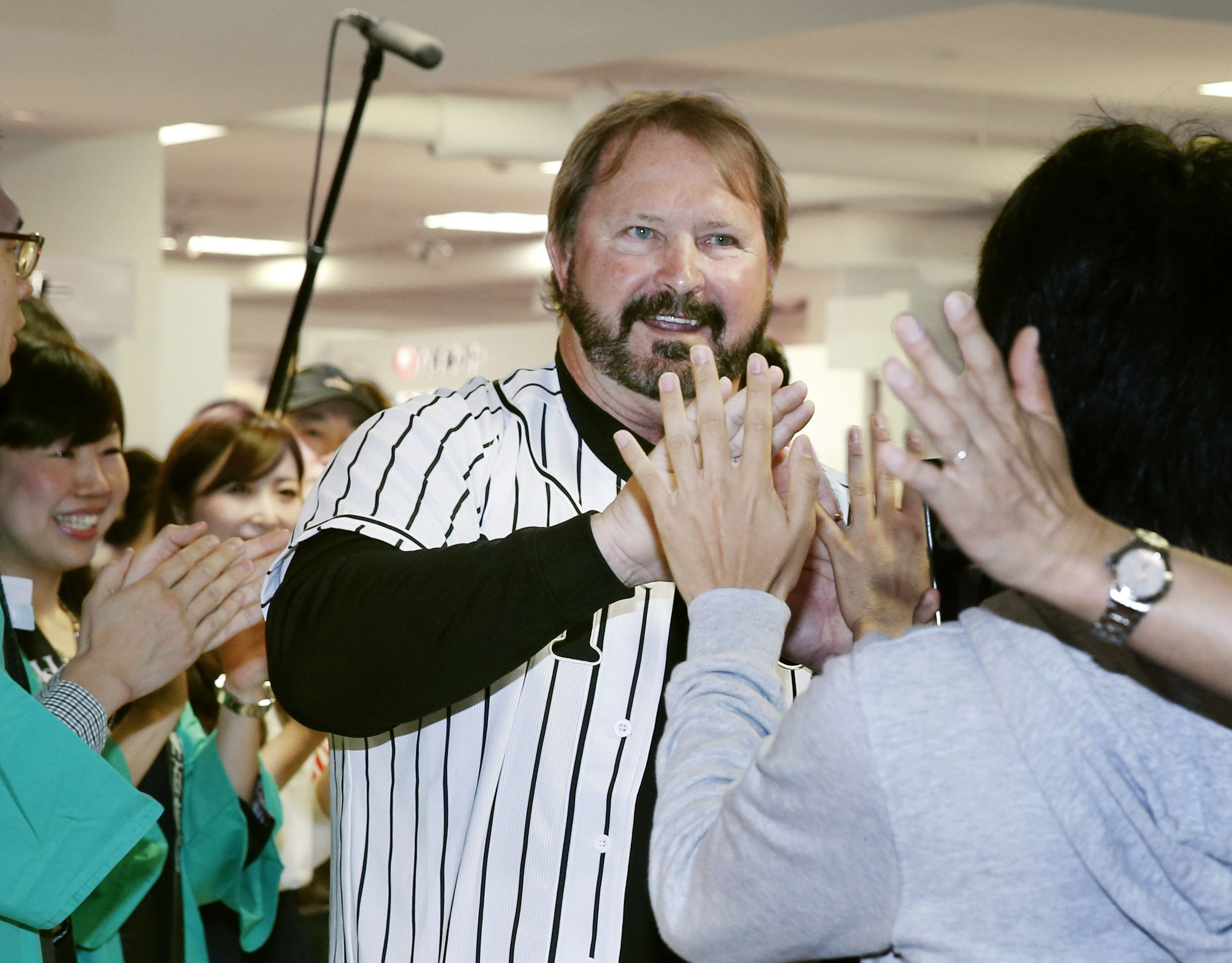 Sen. Randy Bass, D-Okla., wearing Hanshin Tigers' uniform, in greeted by fans during an event at Hanshin Department Store in Osaka, western Japan, Friday, April 17, 2015. Bass was back in Japan, recalling his standout baseball career with the Tigers. The