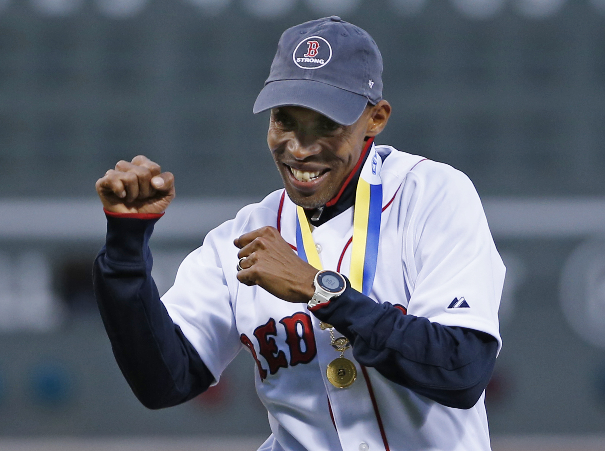 ADVANCE FOR WEEKEND EDITIONS, APRIL  18-19- FILE - In this April 23, 2014, file photo,2014 Boston Marathon winner Meb Keflezighi reacts after throwing a ceremonial first pitch prior to a baseball game between the Boston Red Sox and New York Yankees at Fen