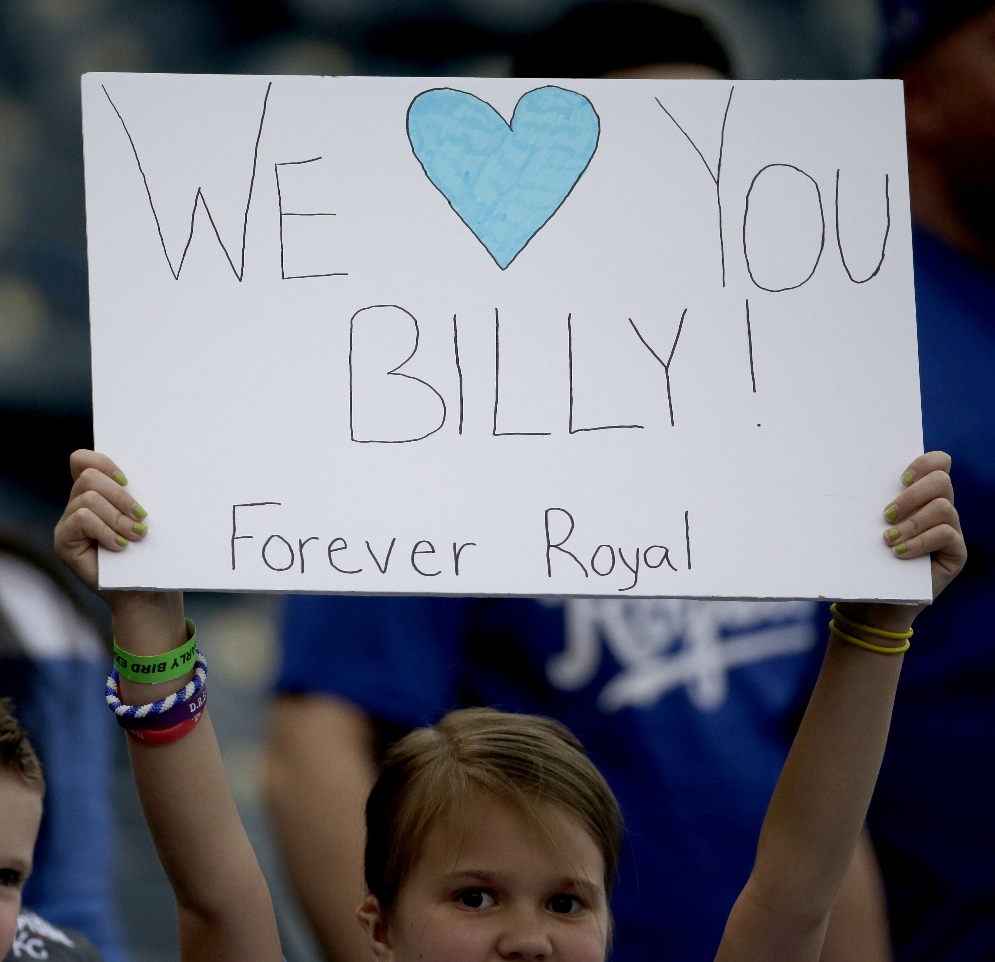 A fan holds a sign referring to the return of former Kansas City Royals player Billy Butler on his first trip back to Kauffman Stadium since being traded to the Oakland Athletics before a baseball game Friday, April 17, 2015, in Kansas City, Mo. (AP Photo