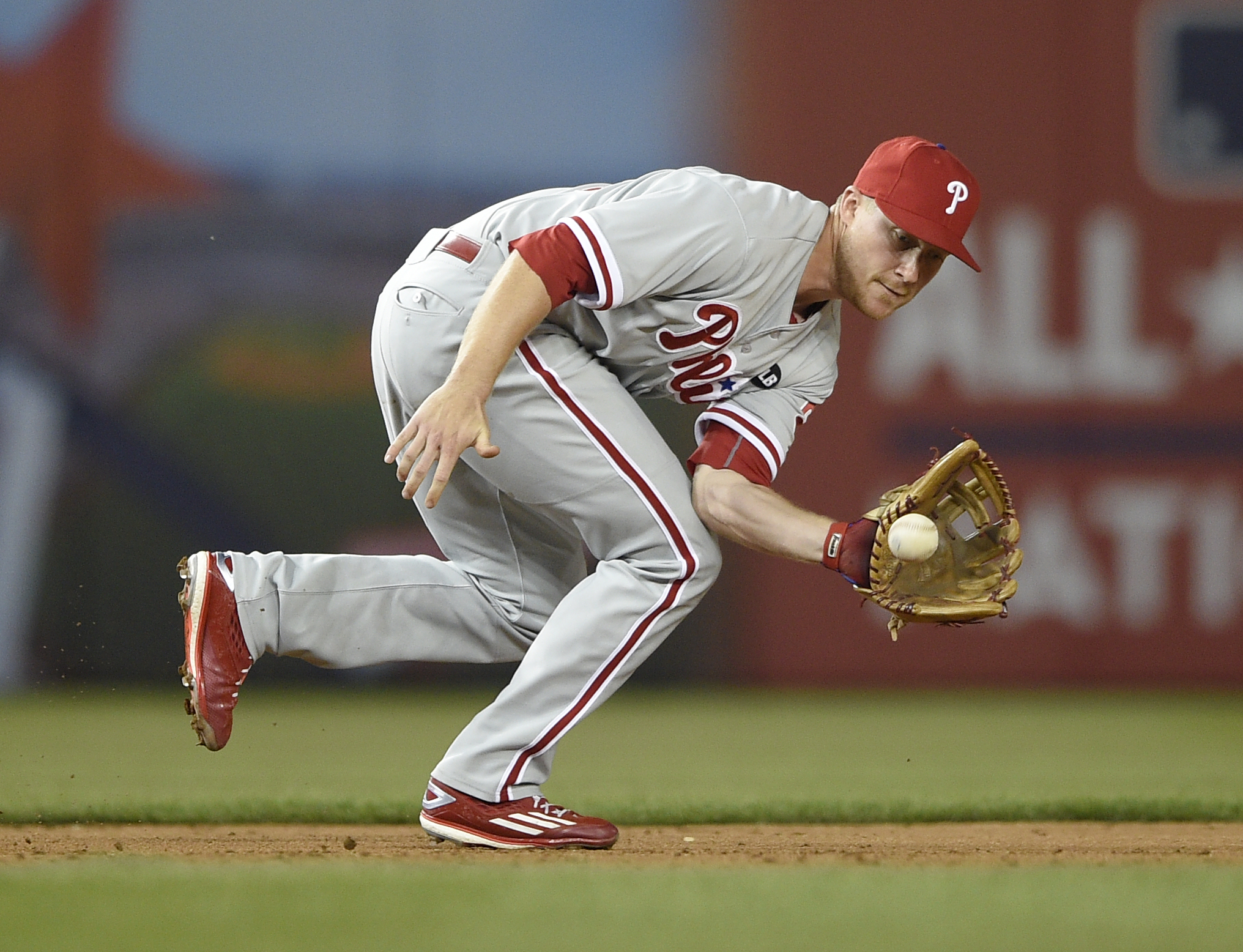 Philadelphia Phillies third baseman Cody Asche (25) fields a ball hit by Washington Nationals' Ian Desmond who reached first on a throwing error by Asche on the play during the fifth inning of a baseball game, Friday, April 17, 2015, in Washington. (AP Ph