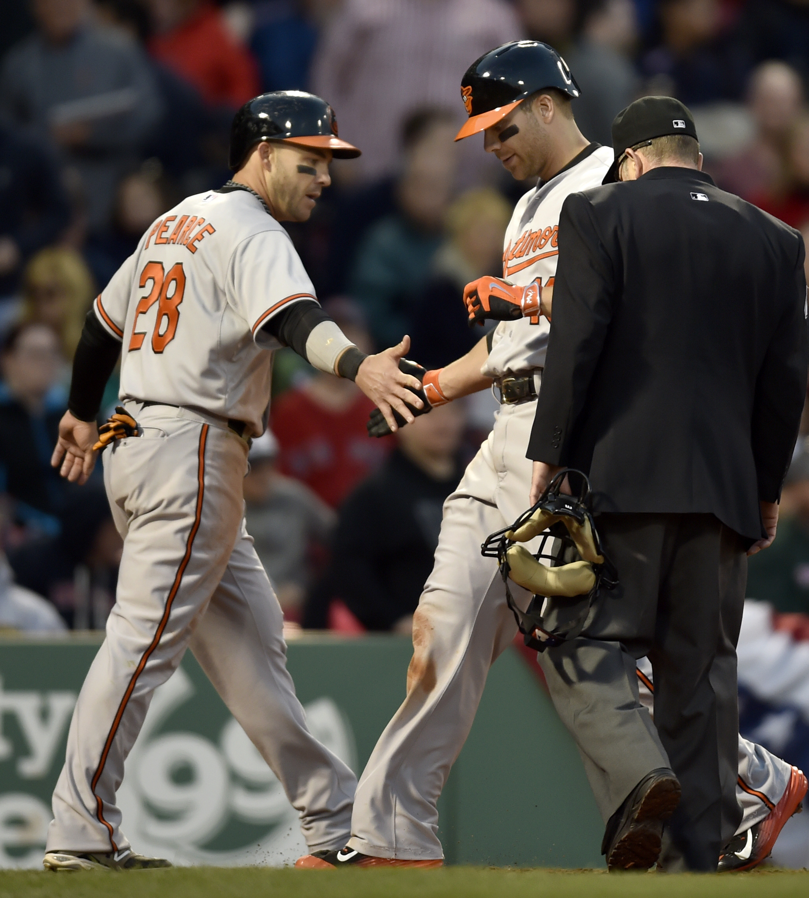 Baltimore Orioles' Chris Davis, center, slaps the hand of teammate Steve Pearce as he crosses home plate after hitting a two-run home run in the ninth inning of a baseball game against the Boston Red Sox, Saturday, April 18, 2015, in Boston. (AP Photo/Gre