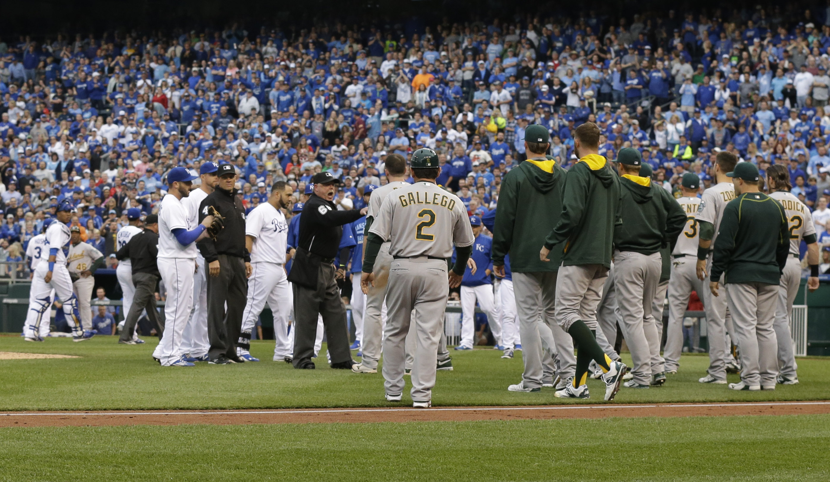 Umpires get between the Oakland Athletics and Kansas City Royals after benches emptied after Oakland Athletics' Brett Lawrie was hit by a pitch during the fourth inning of a baseball game at Kauffman Stadium in Kansas City, Mo., Saturday, April 18, 2015.