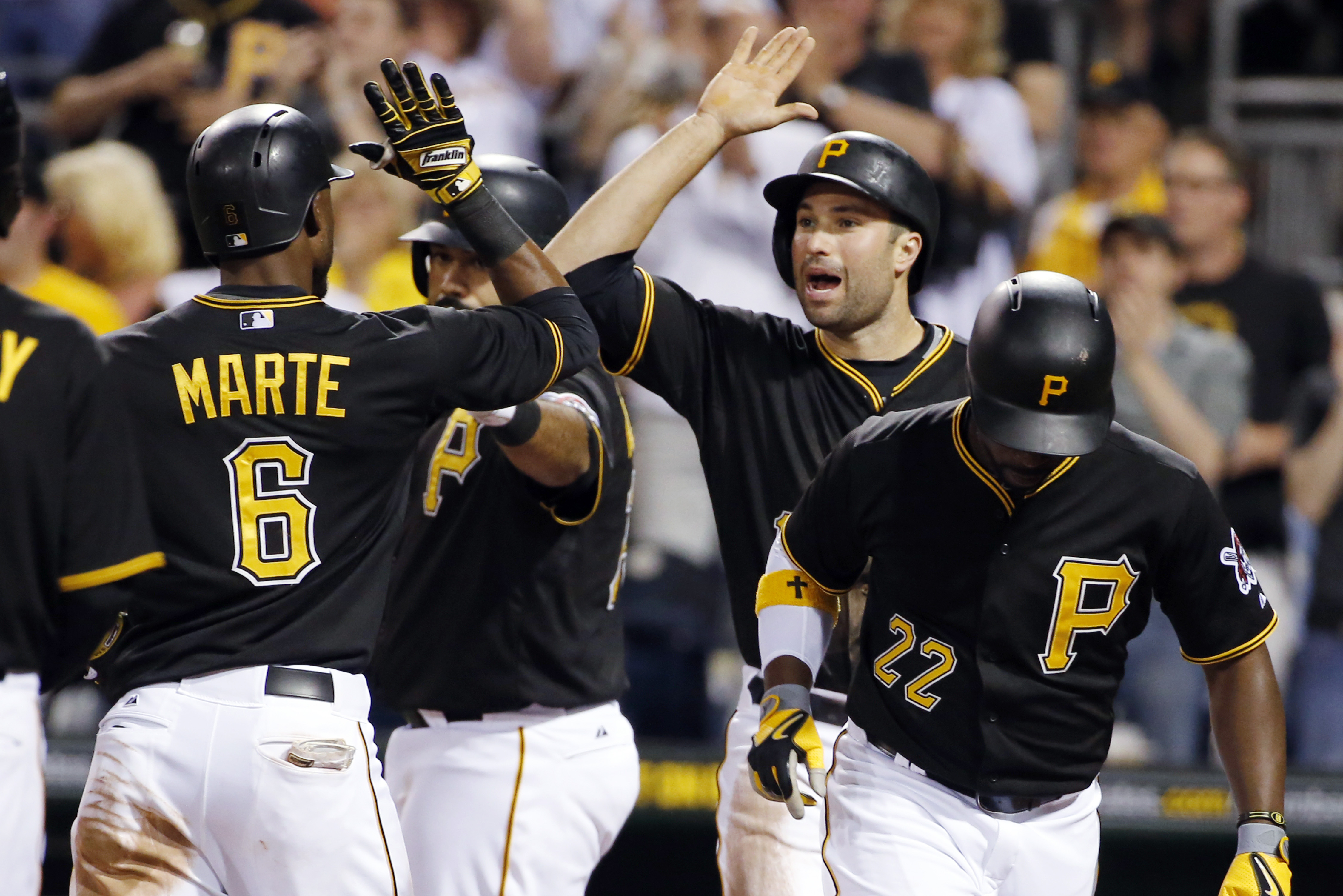 Pittsburgh Pirates' Starling Marte (6) celebrates with Neil Walker, center, as he crosses the plate after hitting a three-run home run off Milwaukee Brewers starting pitcher Kyle Lohse in the fifth inning of a baseball game in Pittsburgh, Saturday, April