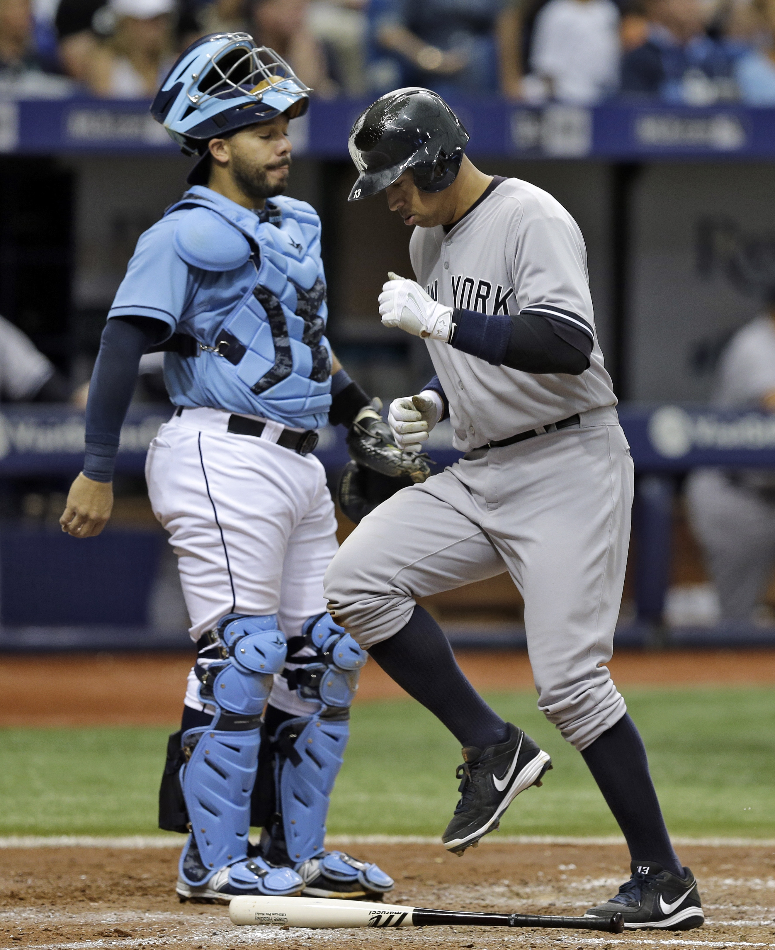New York Yankees' Alex Rodriguez, right, scores in front of Tampa Bay Rays catcher Rene Rivera on an RBI double by Yankees' Chase Headley of Rays pitcher Steven Geltz during the fifth inning of a baseball game Sunday, April 19, 2015, in St. Petersburg, Fl