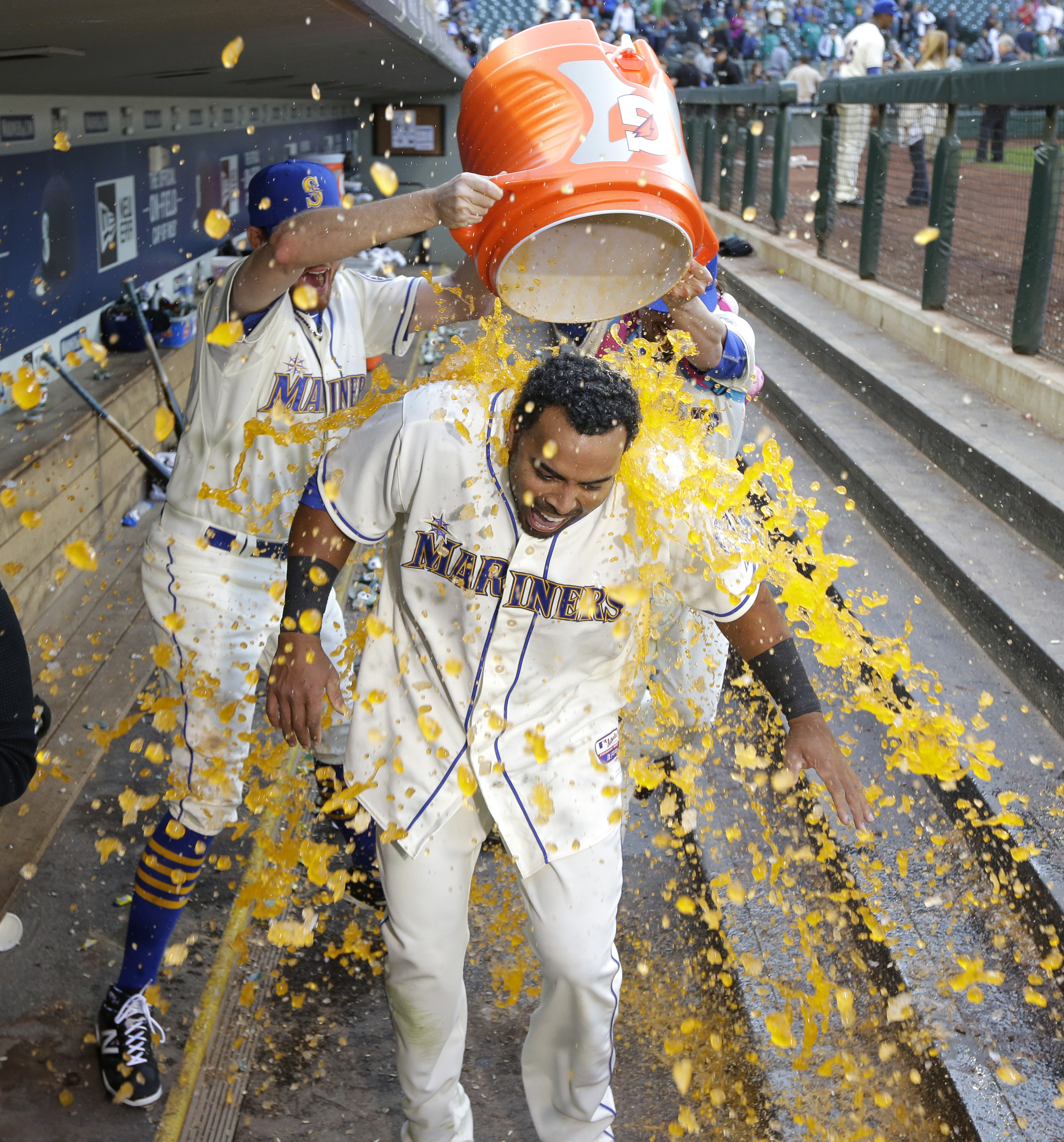 Seattle Mariners' Nelson Cruz, foreground, is doused by Mariners pitchers Charlie Furbush, left, and Danny Farquhar, right, as he takes part in a television interview after hitting a walkoff RBI-single in the ninth inning of a baseball game against the Te