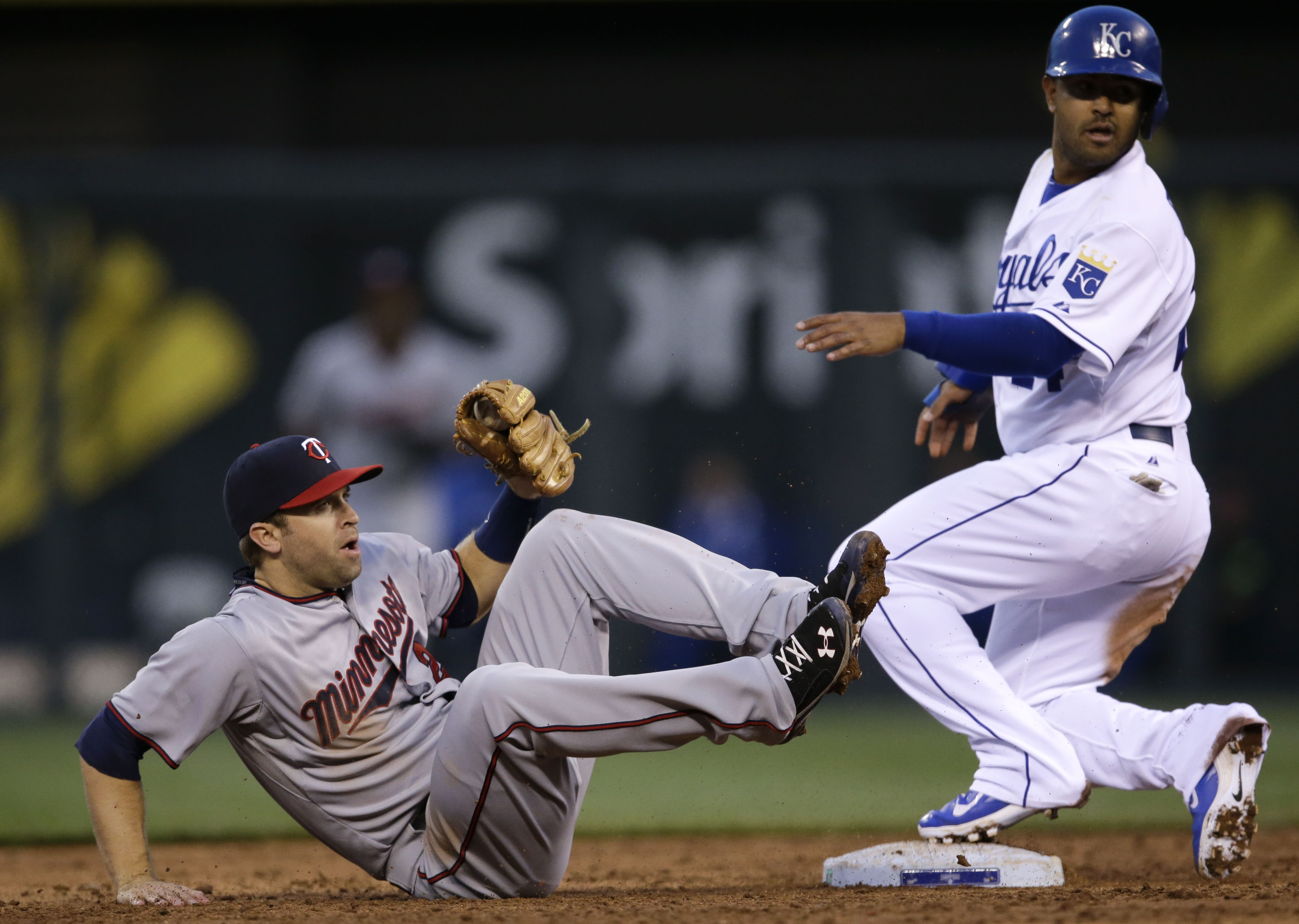 Minnesota Twins second baseman Brian Dozier, left, falls to the ground after forcing out Kansas City Royals' Christian Colon, right, during the second inning of a baseball game at Kauffman Stadium in Kansas City, Mo., Monday, April 20, 2015. (AP Photo/Orl