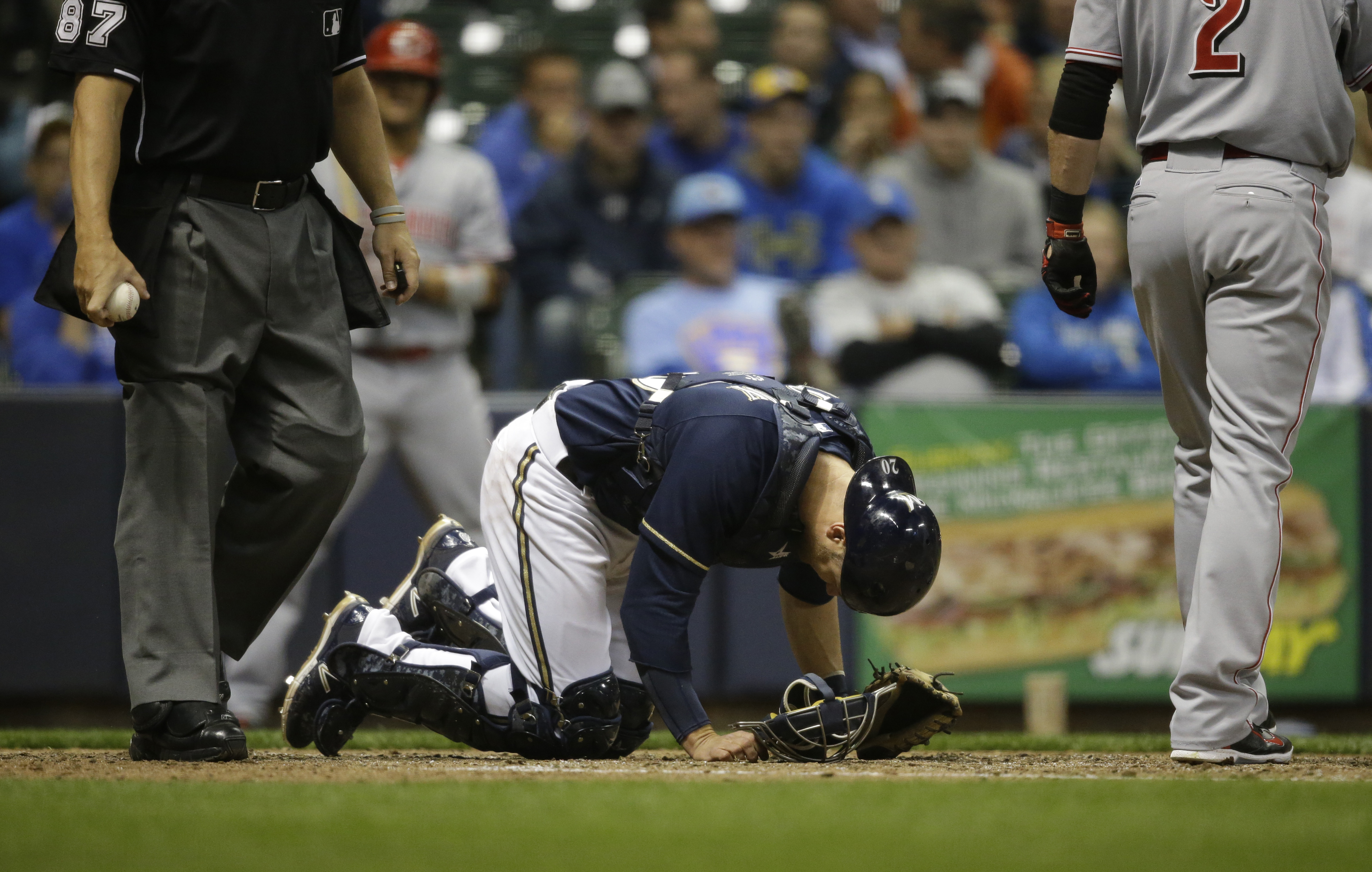 Milwaukee Brewers catcher Jonathan Lucroy bends over after taking a foul tip off his toe during the sixth inning of a baseball game  against the Cincinnati Reds Monday, April 20, 2015, in Milwaukee. Lucroy left the game and the Brewers announced after the