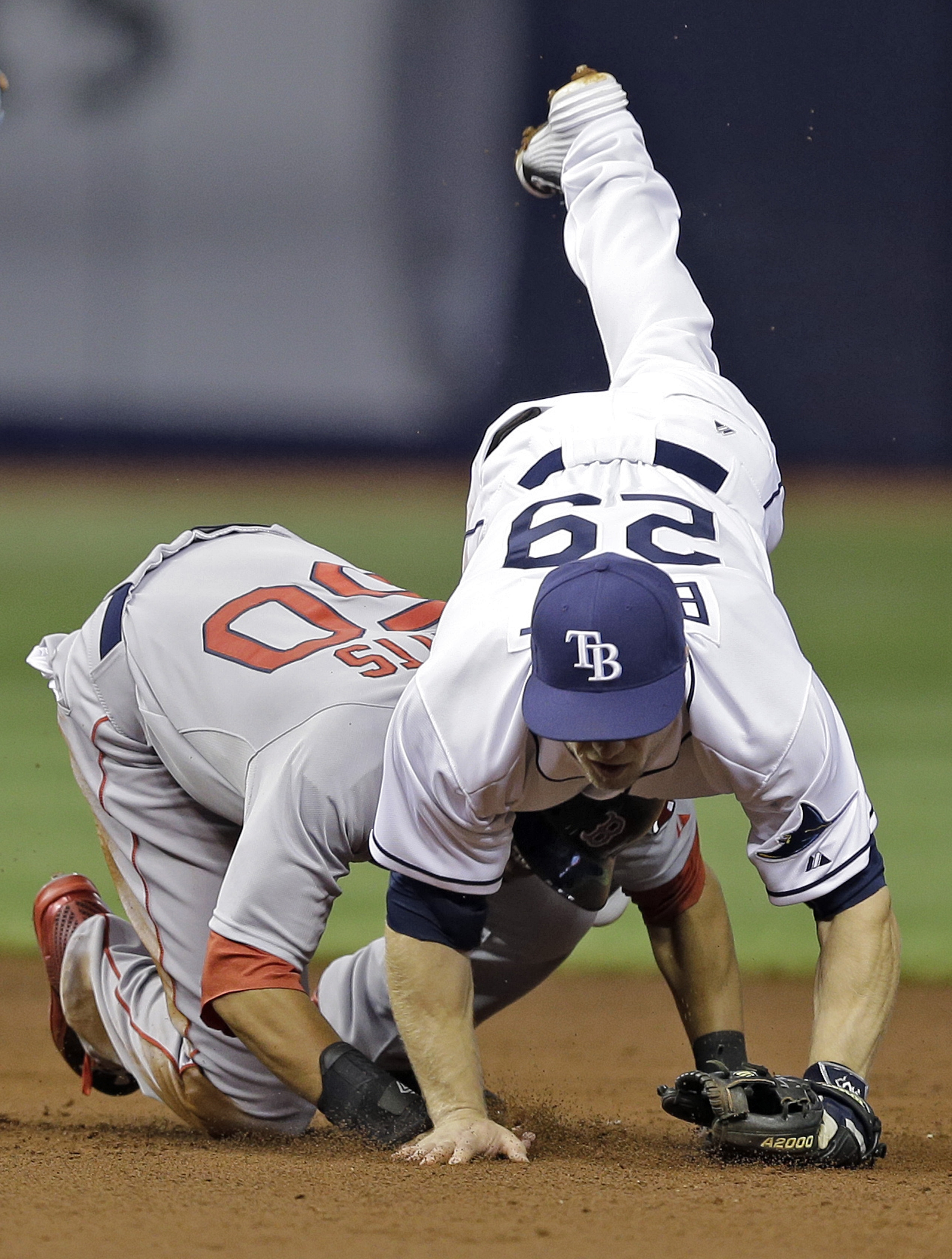 Boston Red Sox's Mookie Betts (50) upends Tampa Bay Rays second baseman Ryan Brett on a fielder's choice by Dustin Pedroia during the third inning of a baseball game Tuesday, April 21, 2015, in St. Petersburg, Fla. A wild throw by Brett allowed Ryan Hanig