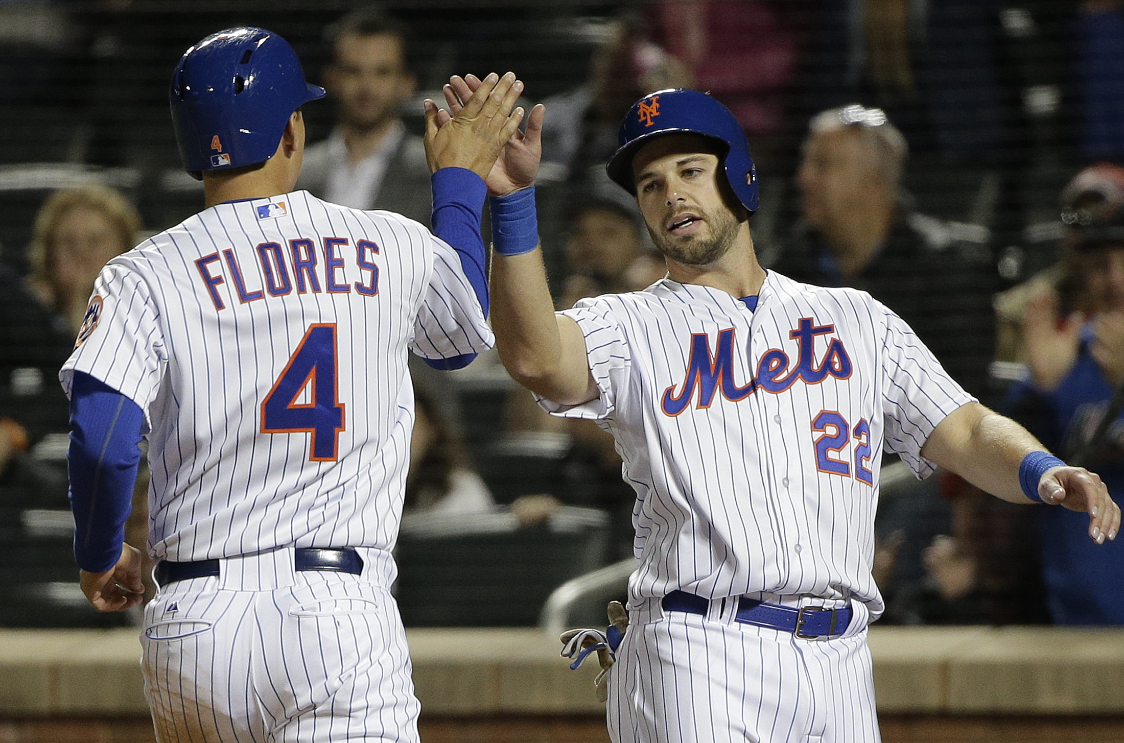 New York Mets' Kevin Plawecki (22) greets Wilmer Flores (4) after the two scored on a hit by Curtis Granderson against the Atlanta Braves in the fifth inning of a baseball game, Tuesday, April 21, 2015, in New York. (AP Photo/Julie Jacobson)