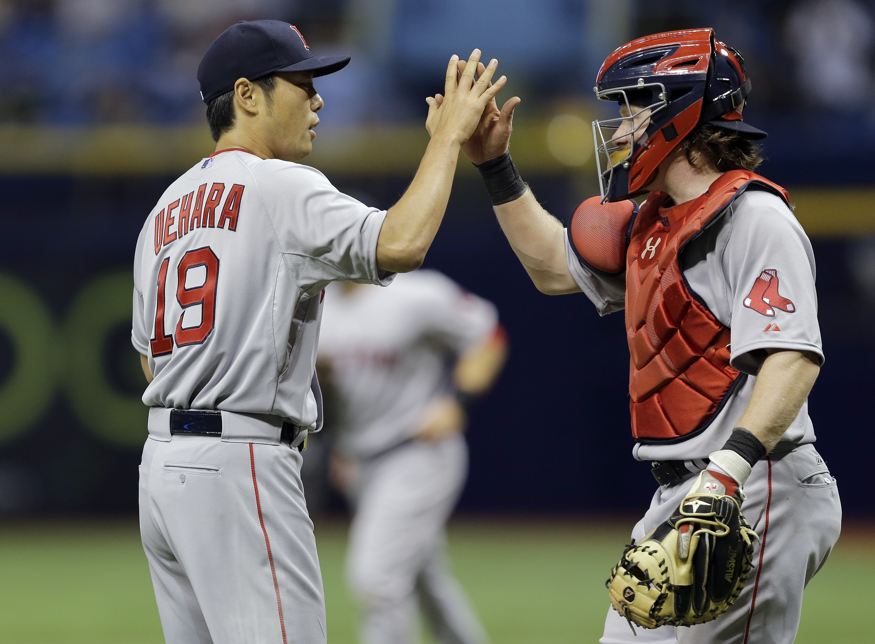 Boston Red Sox relief pitcher Koji Uehara, left, of Japan, high fives catcher Ryan Hanigan after closing out the Tampa Bay Rays during the ninth inning of a baseball game Tuesday, April 21, 2015, in St. Petersburg, Fla. Uehara picked up the save in the Re