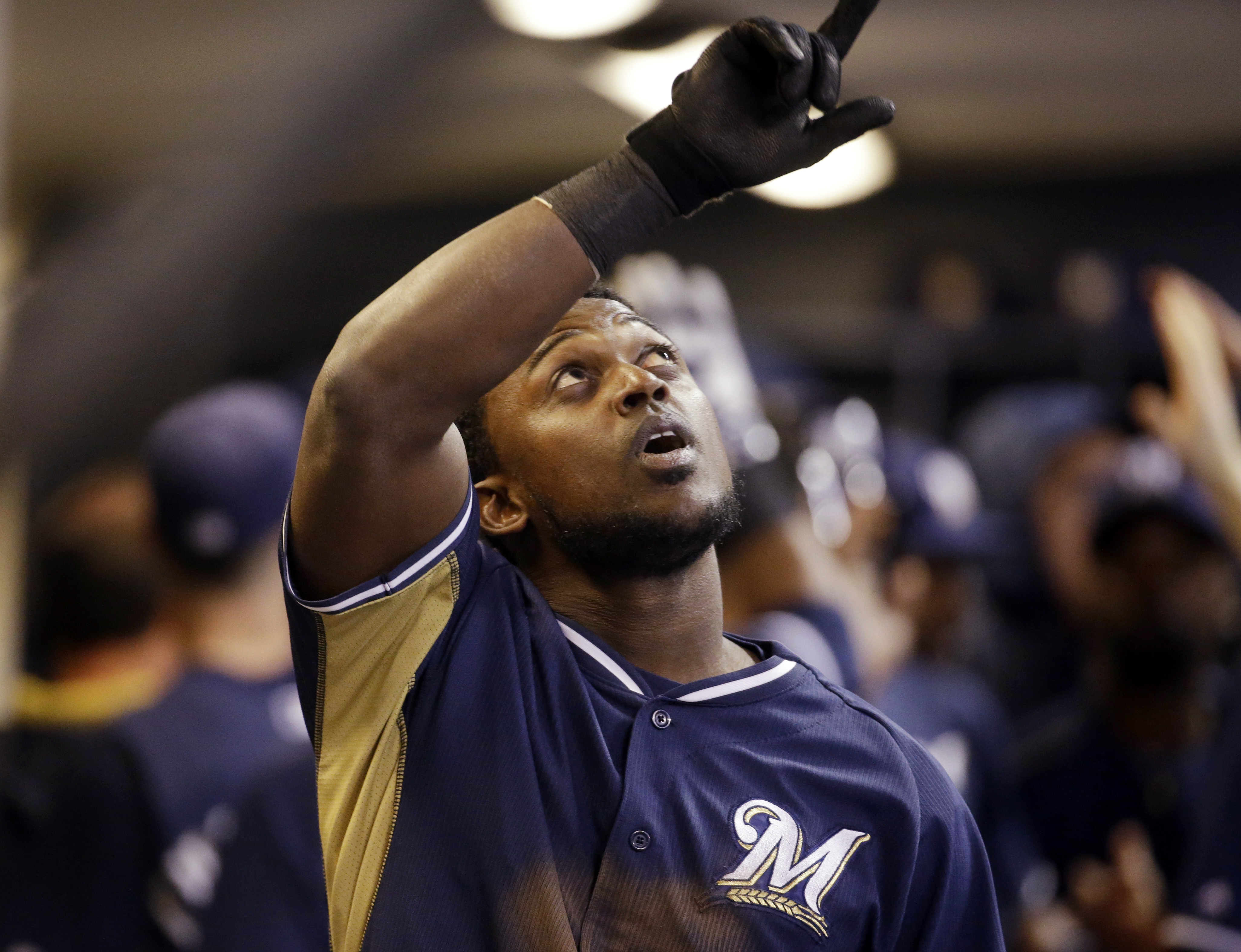 Milwaukee Brewers' Elian Herrera celebrates in the dugout after hitting a grand slam during the sixth inning of a baseball game against the Cincinnati Reds on Tuesday, April 21, 2015, in Milwaukee. (AP Photo/Morry Gash)