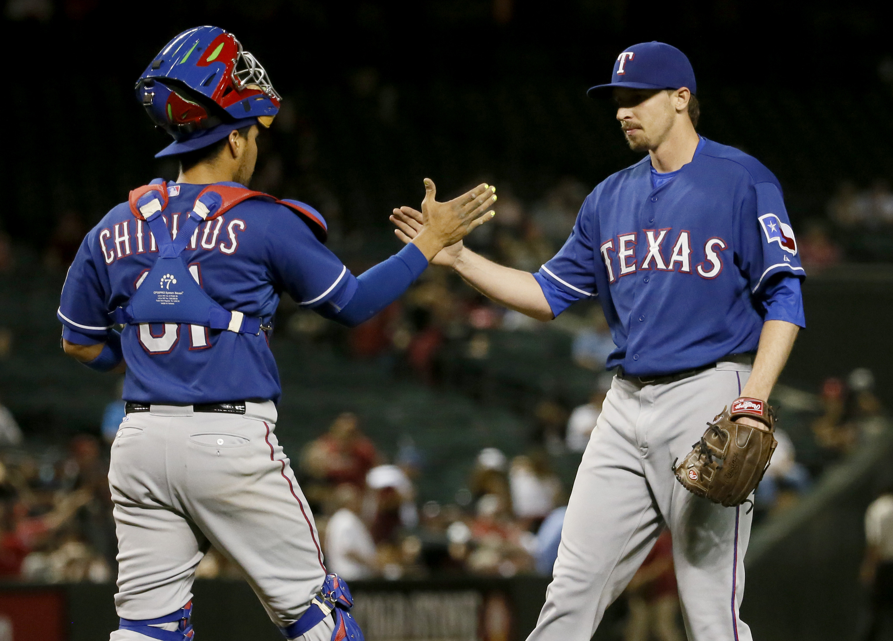 Texas Rangers catcher Robinson Chirinos, left, greets relief pitcher Tanner Scheppers after a baseball game against the Arizona Diamondbacks, Tuesday, April 21, 2015, in Phoenix.  The Rangers won 7-1. (AP Photo/Matt York)