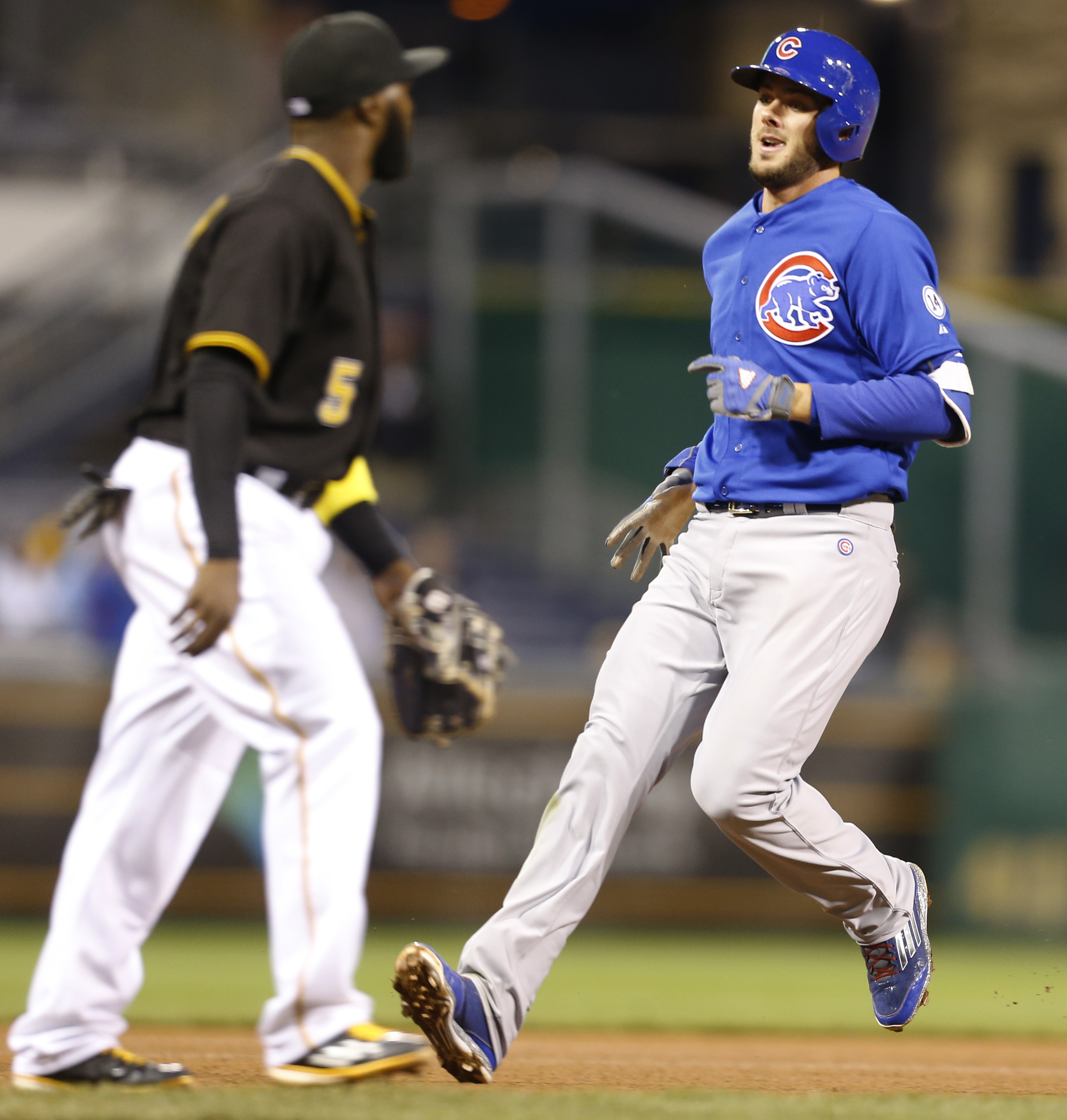 Chicago Cubs' Kris Bryant, right, trots into third as Pittsburgh Pirates third baseman Josh Harrison looks for the ball in the fourth inning of a baseball game on Wednesday, April 22, 2015, in Pittsburgh. Bryant hit a fly ball between right fielder Gregor