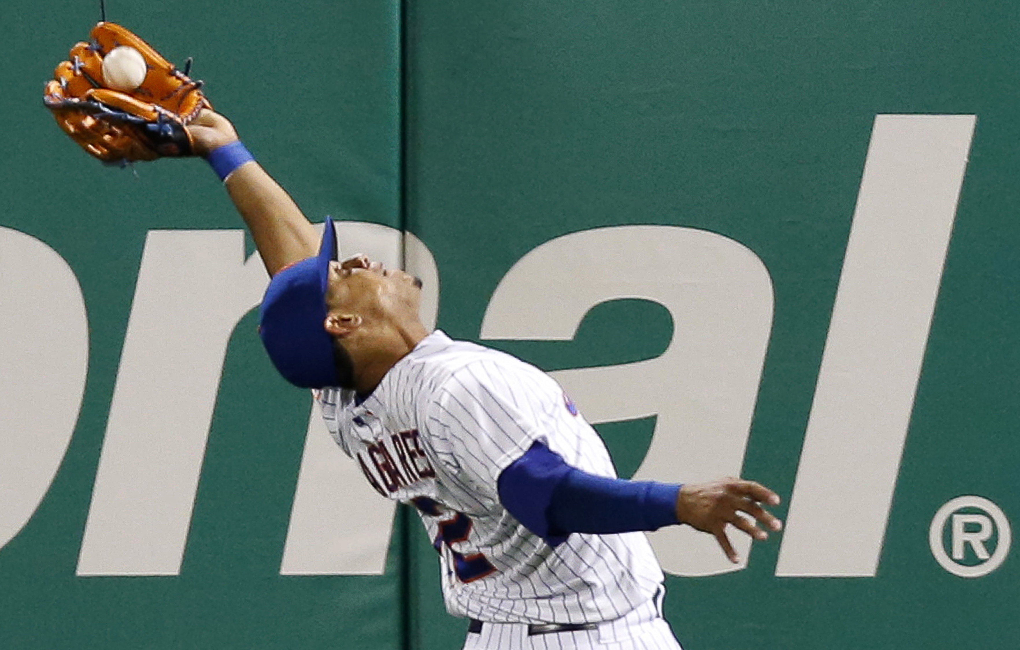 New York Mets center fielder Juan Lagares (12) makes a seventh-inning, over-the-shoulder catch on a flyout by Atlanta Braves Jace Peterson in a baseball game in New York, Wednesday, April 22, 2015. (AP Photo/Kathy Willens)