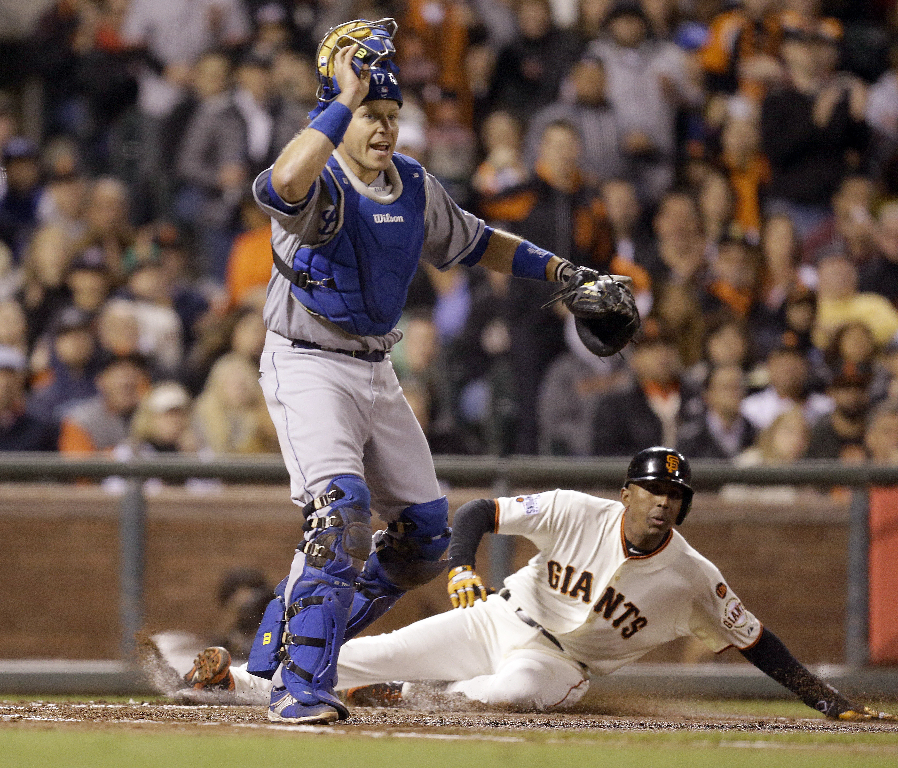 San Francisco Giants' Joaquin Arias, right, slides to score behind Los Angeles Dodgers catcher A.J. Ellis during the third inning of a baseball game Wednesday, April 22, 2015, in San Francisco. Arias scored on a ground out by Nori Aoki. (AP Photo/Ben Marg