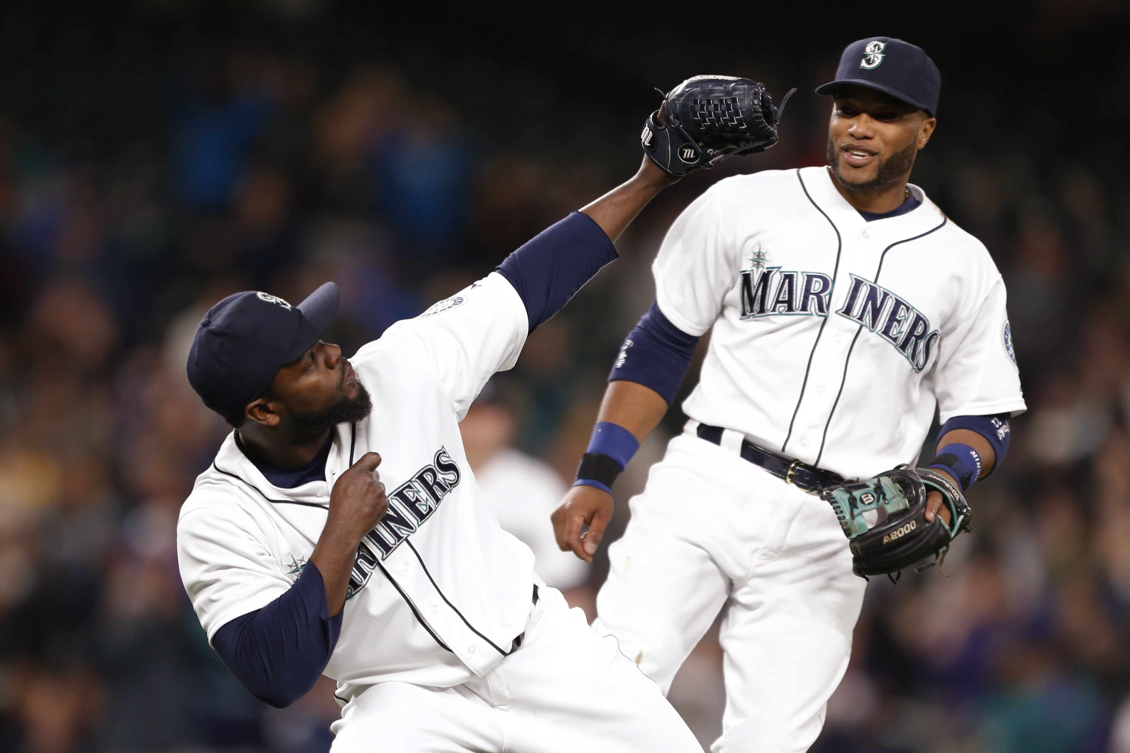Seattle Mariners pitcher Fernando Rodney, left, and second baseman Robinson Cano celebrate the Mariners' 3-2 win over the Houston Astros in a baseball game Wednesday, April 22, 2015, in Seattle. (AP Photo/Jennifer Buchanan)