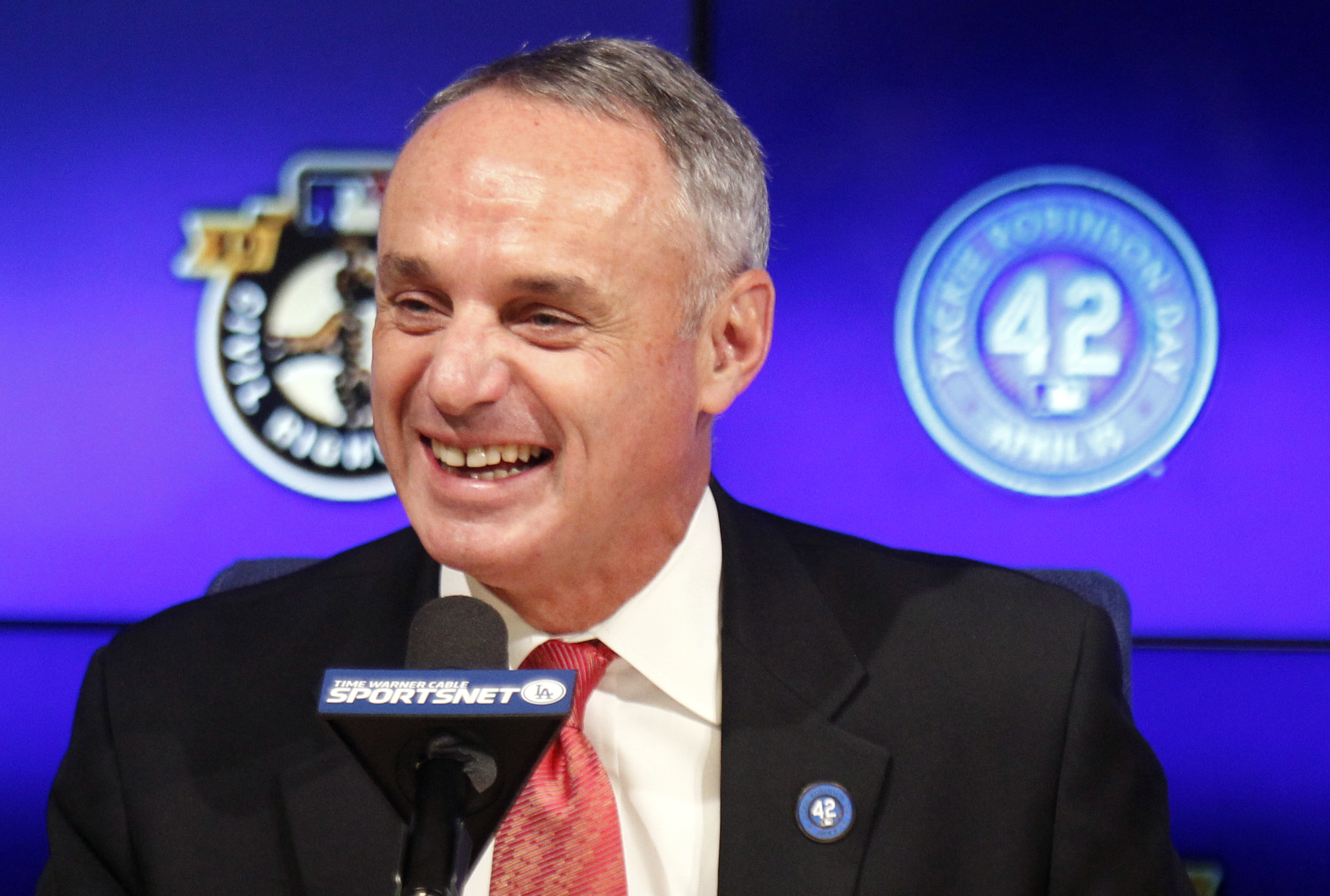 FILE - In this April 15, 2015, file photo, Major League Baseball Commissioner Rob Manfred talks during a news conference prior to a baseball game between the Los Angeles Dodgers and the Seattle Mariners on Jackie Robinson Day in Los Angeles. Manfred said
