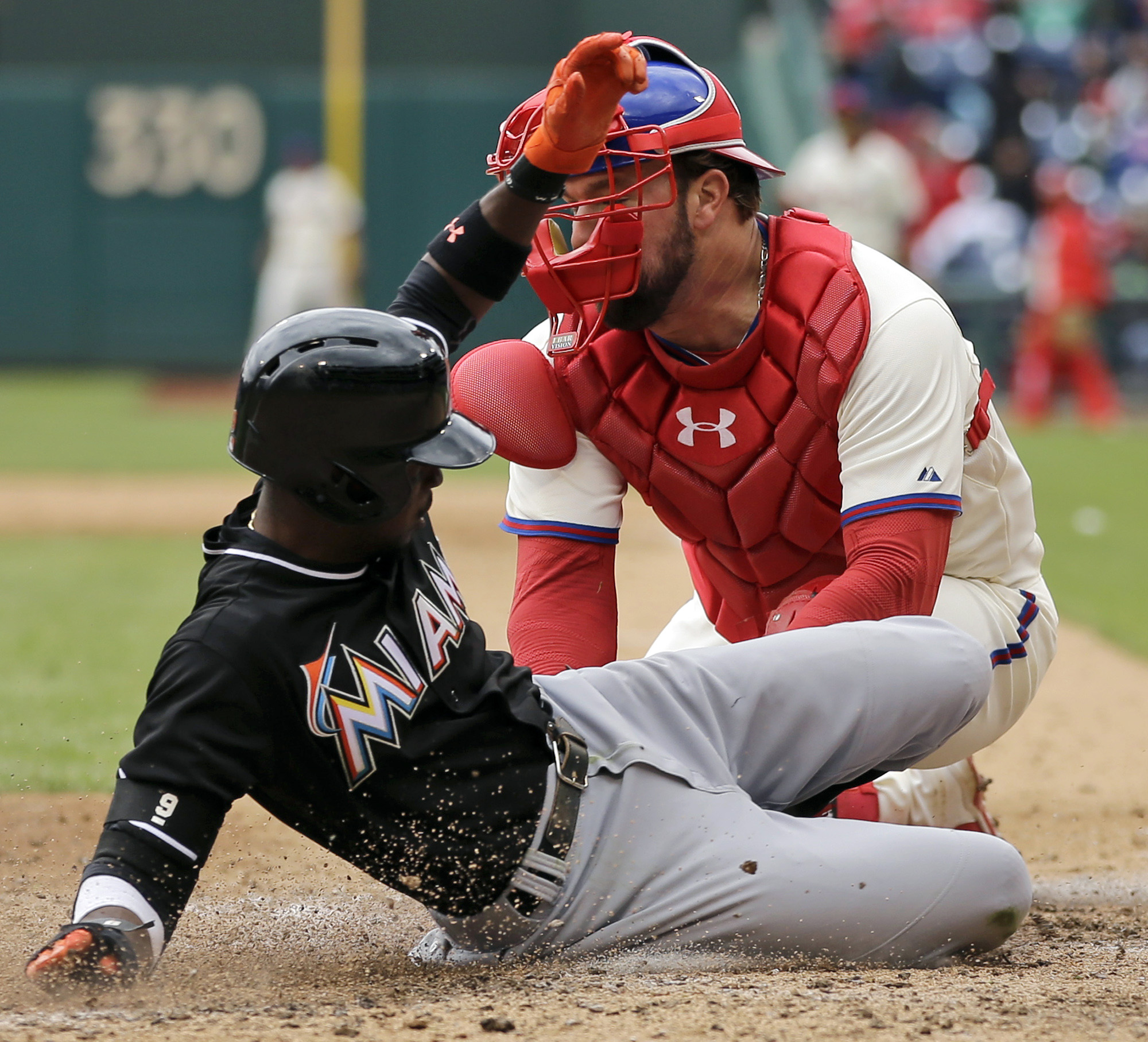 Miami Marlins' Dee Gordon, left, scores past the tag from Philadelphia Phillies catcher Cameron Rupp on a two-run double by Martin Prado during the sixth inning of a baseball game, Thursday, April 23, 2015, in Philadelphia. (AP Photo/Matt Slocum)
