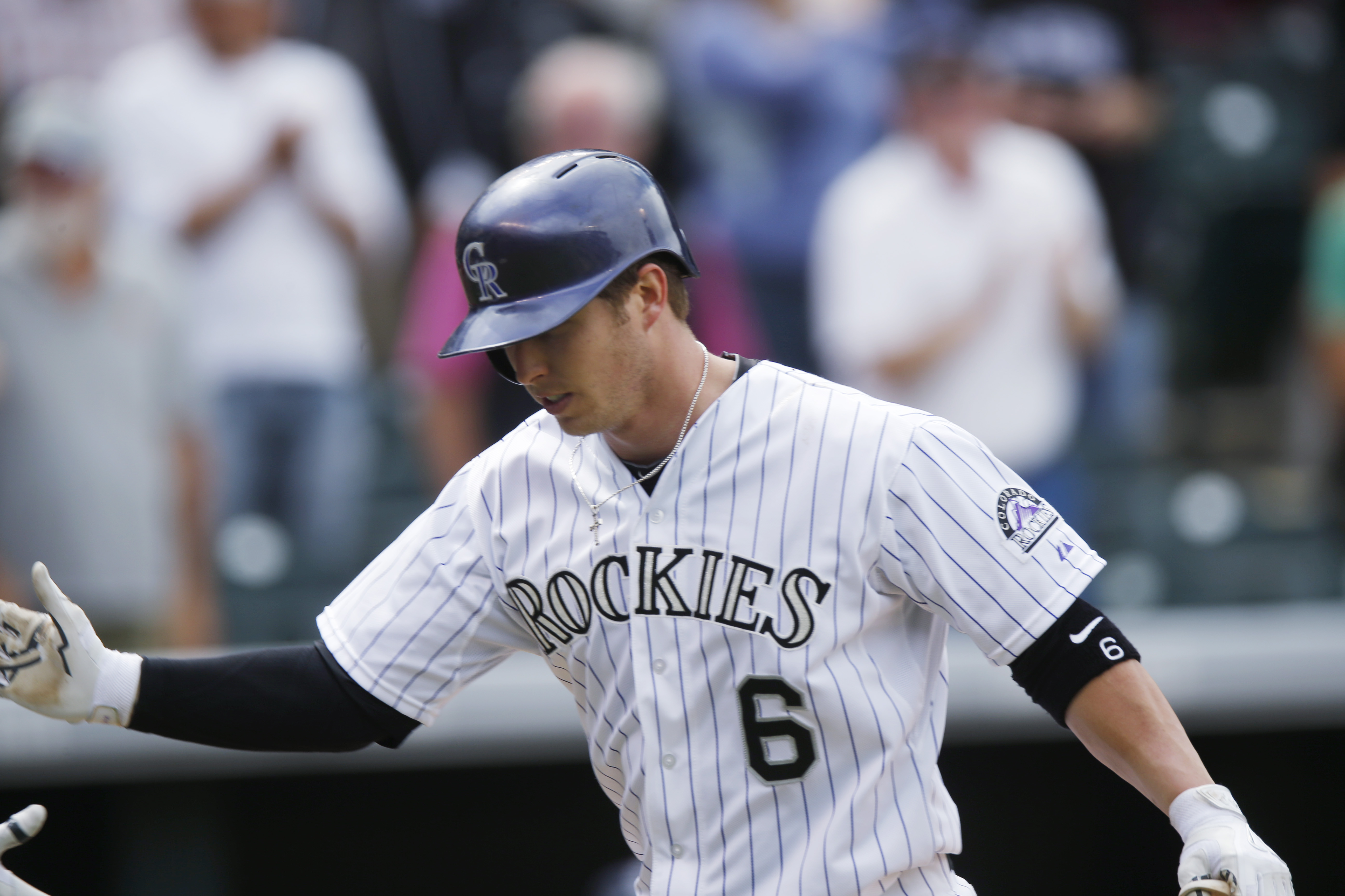 Colorado Rockies' Corey Dickerson is congratulated after hitting a solo home run against the San Diego Padres in the fifth inning of a baseball game Thursday, April 23, 2015, in Denver. (AP Photo/David Zalubowski)