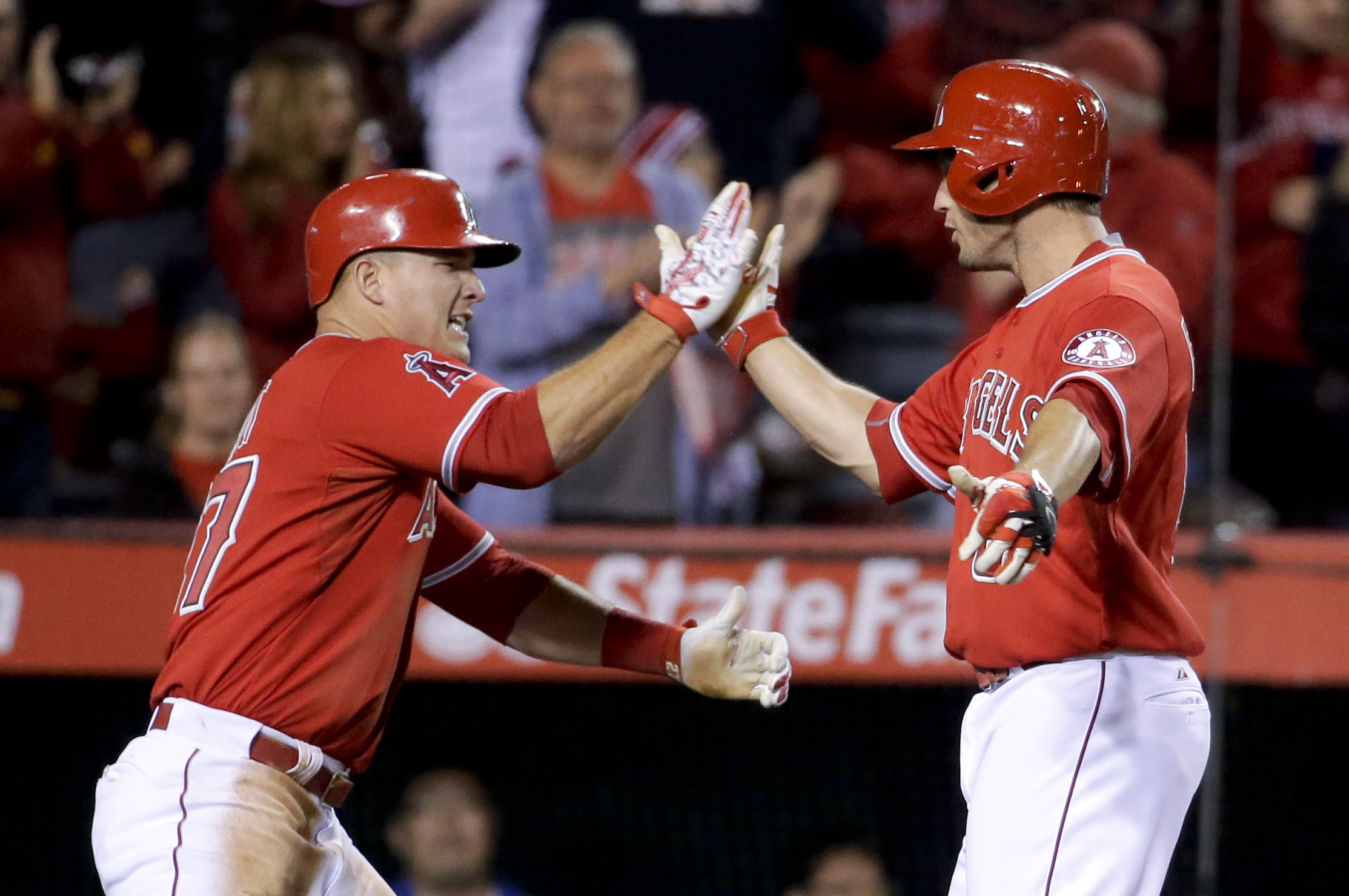 Los Angeles Angels' David Freese, right, celebrates his two-run home run with Mike Trout against the Texas Rangers during the seventh inning of a baseball game in Anaheim, Calif., Friday, April 24, 2015. (AP Photo/Chris Carlson)