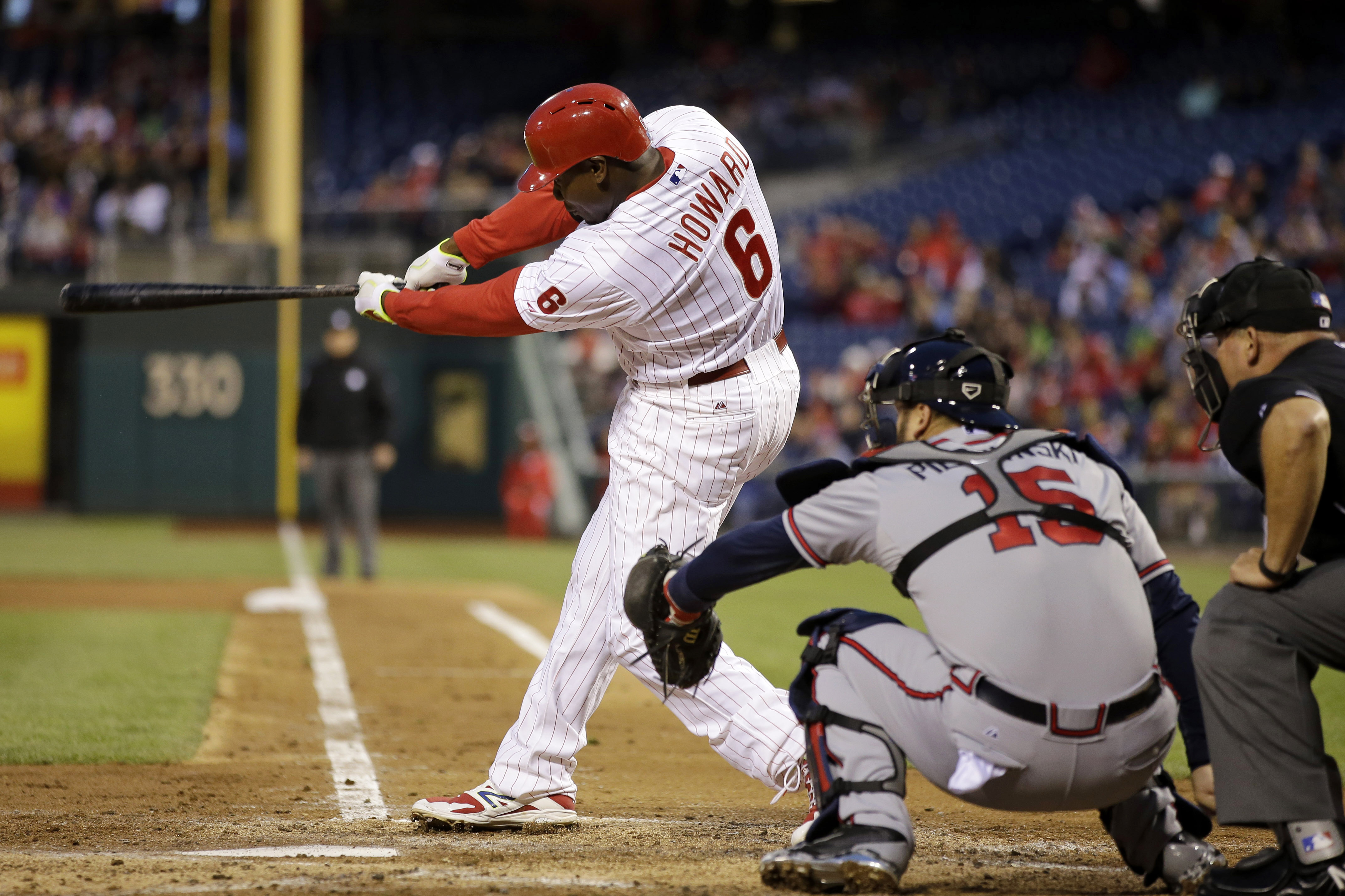 Philadelphia Phillies' Ryan Howard follows through on a two-run home run off Atlanta Braves starting pitcher Shelby Miller as catcher A.J. Pierzynski, center, and umpire Mark Carlson watch during the fourth inning of a baseball game, Saturday, April 25, 2