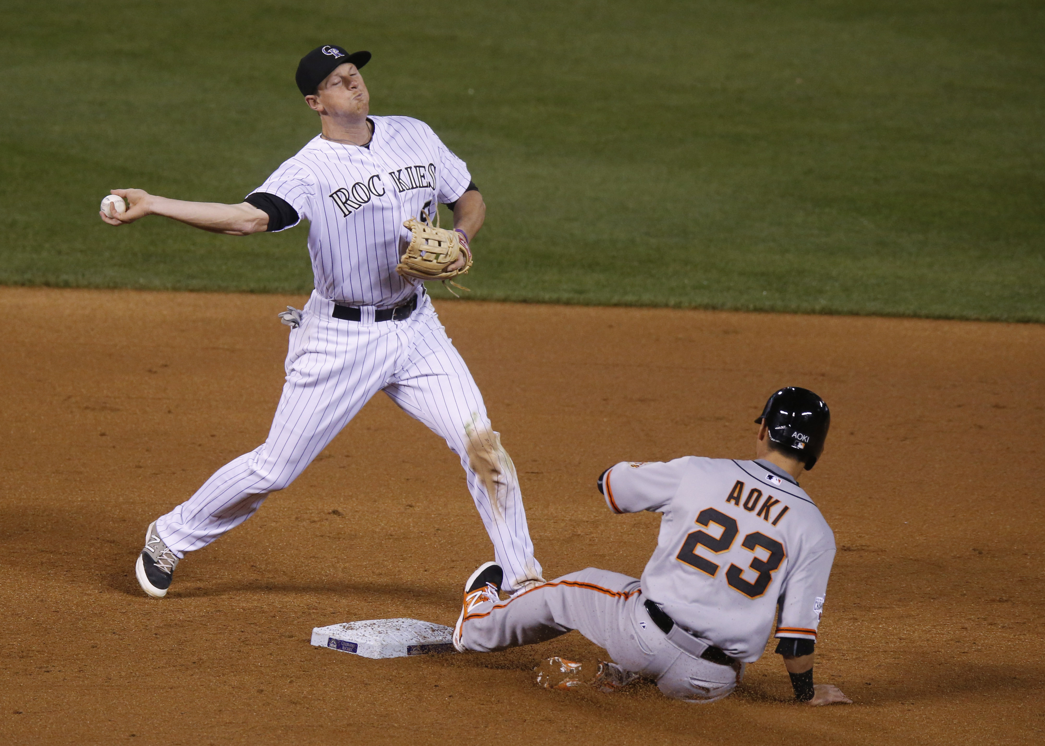 Colorado Rockies second baseman DJ LeMahieu, left, throws to first base after forcing out San Francisco Giants' Nori Aoki at second base in the ninth inning of a baseball game Saturday, April 25, 2015, in Denver. The Giants' Matt Duffy was safe at first b