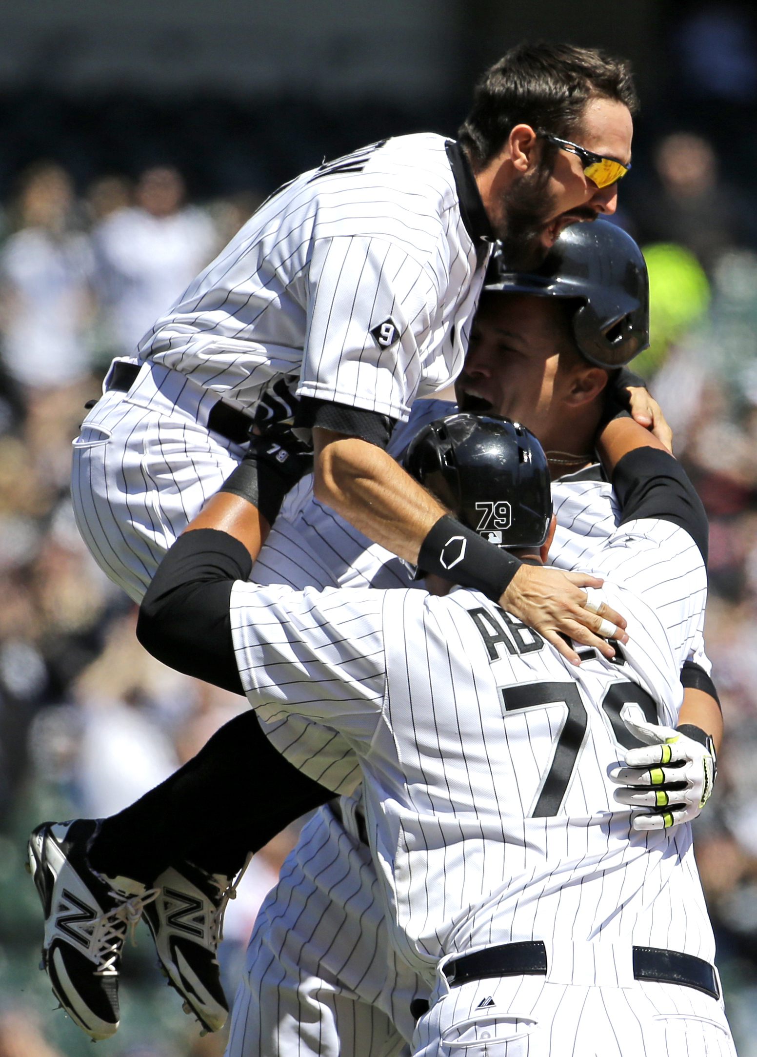 Chicago White Sox's Avisail Garcia, right, celebrates with Adam Eaton, top, and Jose Abreu, foreground, after hitting a game-winning single against the Kansas City Royals during the ninth inning of a continuation of a suspended baseball game from Friday i
