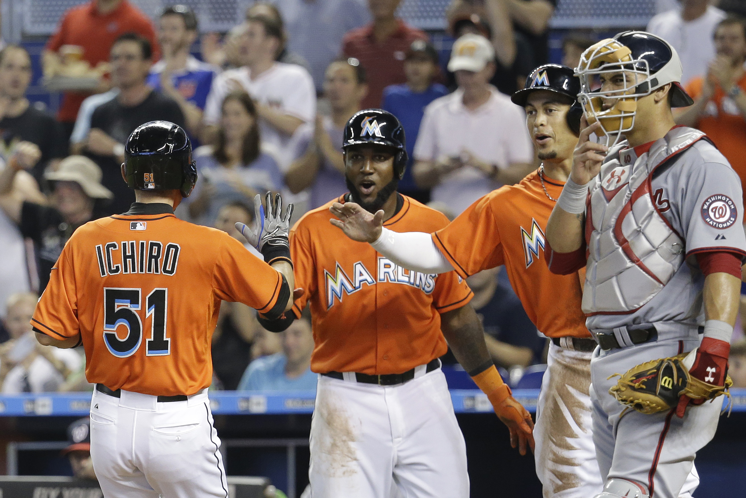 Miami Marlins' Ichiro Suzuki (51) is met by Marcell Ozuna, center, and Giancarlo Stanton, second from right, after they scored on a triple hit by Adeiny Hechavarria in the fourth inning of a baseball game, Sunday, April 26, 2015, in Miami. At right is Was