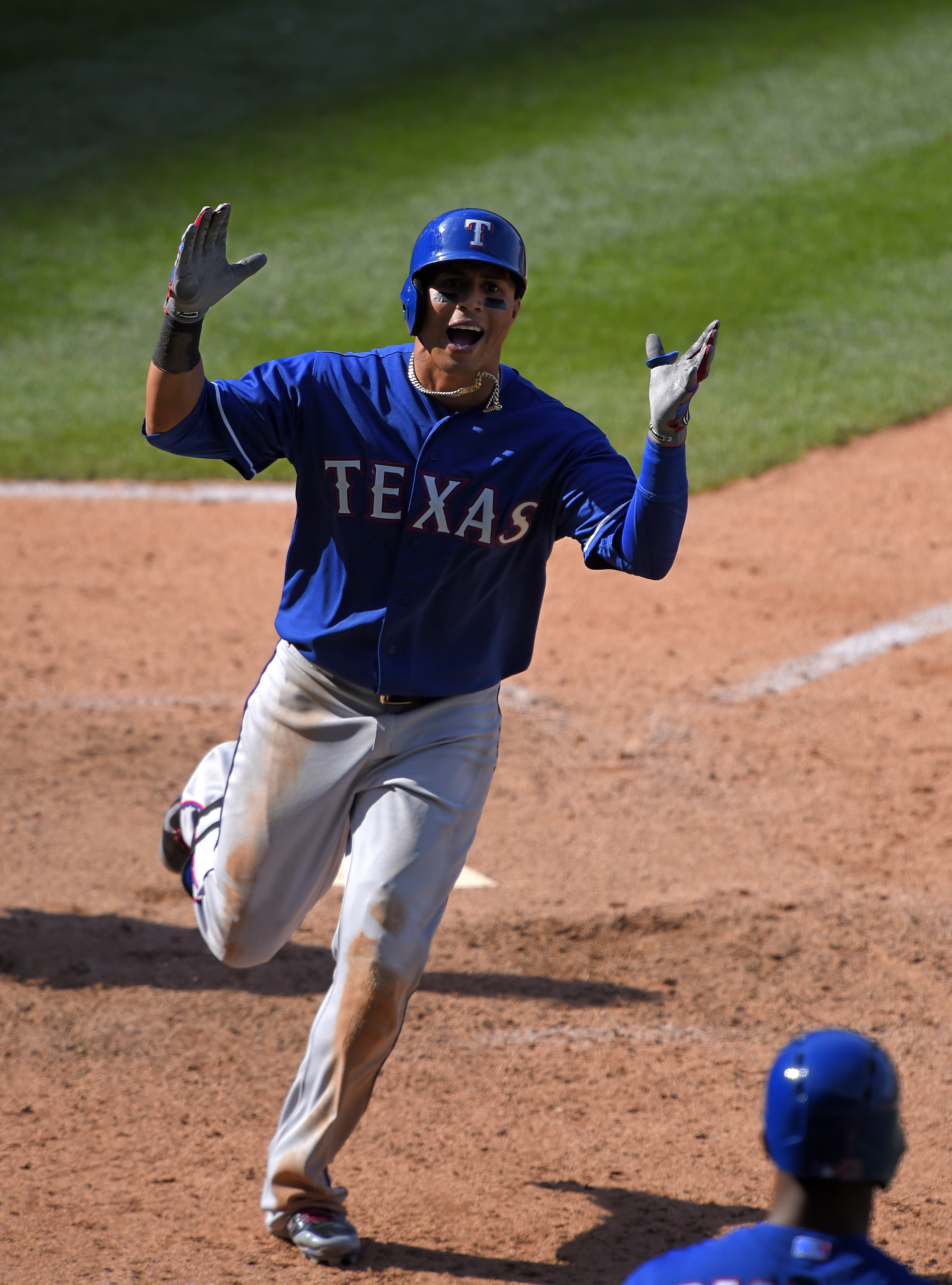 Texas Rangers' Leonys Martin, top, celebrates toward Carlos Peguero after hitting a solo home run during the 11th inning of a baseball game against the Los Angeles Angels, Sunday, April 26, 2015, in Anaheim, Calif. The Rangers won 5-4. (AP Photo/Mark J. T