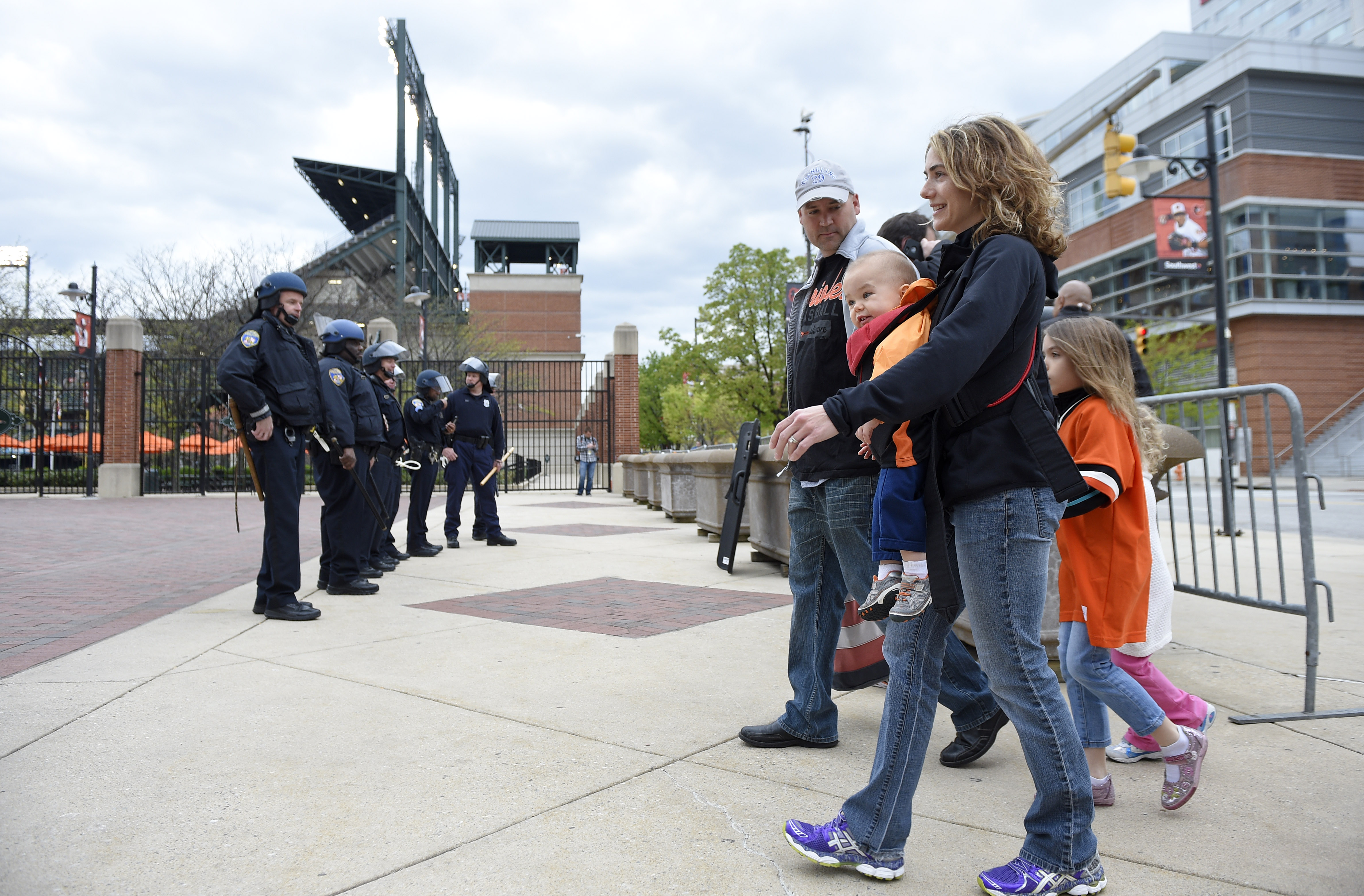 Baseball fans make their way towards Oriole Park at Camden Yards as Baltimore police stand watch, Monday, April 27, 2015, in Baltimore. The baseball game between the Baltimore Orioles and the Chicago White Sox is postponed. (AP Photo/Nick Wass)