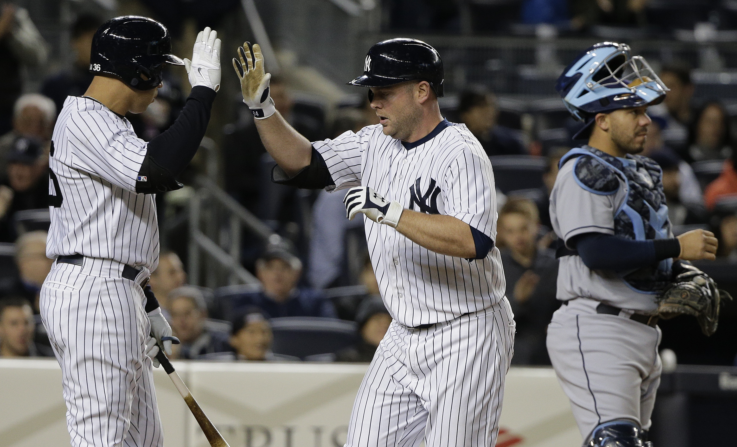 New York Yankees Brian McCann, right, is greeted by designated hitter Carlos Beltran  after hitting a solo home run against the Tampa Bay Rays in the sixth inning of a baseball game, Monday, April 27, 2015, in New York. (AP Photo/Julie Jacobson)